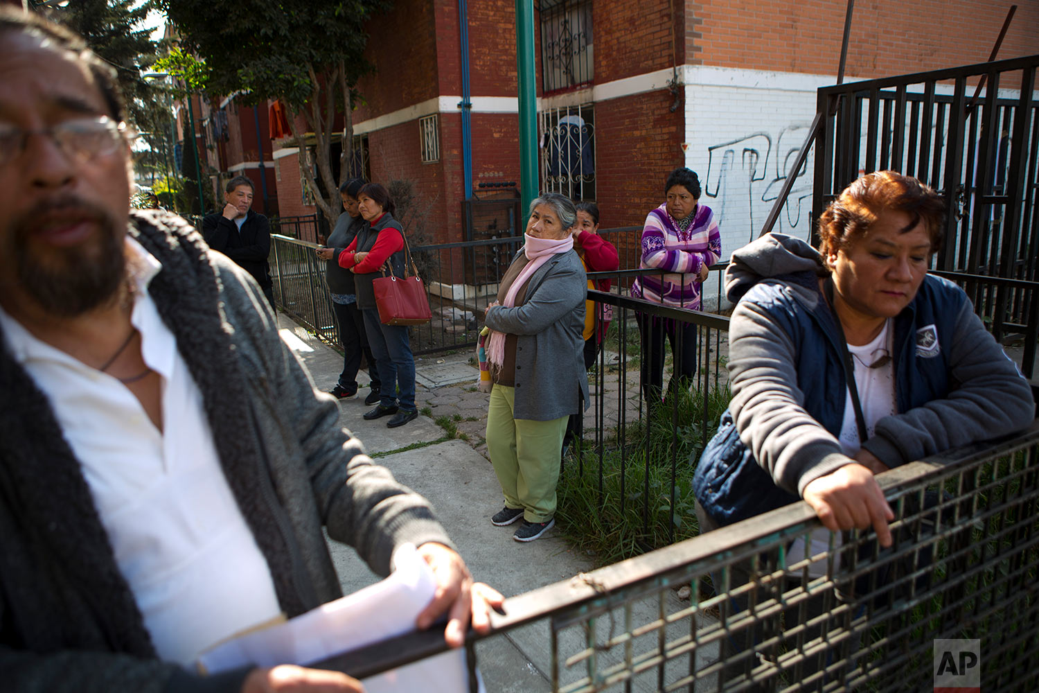 In this Jan. 19, 2018 photo, Veronica Martinez Hernandez, right, and Emmanuel Garcia Carbajal, left, stand along with other neighbors outside the condemned and chained up housing blocks where they lived until September's earthquake, in a housing complex at Ignacio Zaragoza 2980 in eastern Mexico City. Residents say the government has offered no information or help since saying six of their housing blocks will have to be demolished without being rebuilt. (AP Photo/Rebecca Blackwell)