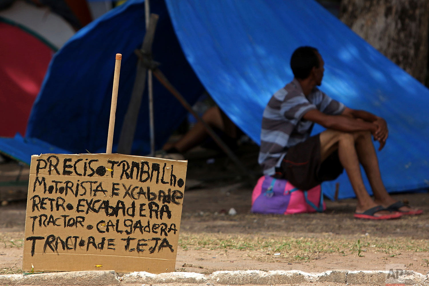 """A sign that reads in Portuguese: """"I need work. Tractor driver. Excavator."""" stands near a Venezuelan migrant outside his tent in Simon Bolivar Square where many Venezuelans have set up tents in Boa Vista, Roraima, Brazil, March 11, 2018. (AP Photo/Eraldo Peres)"""
