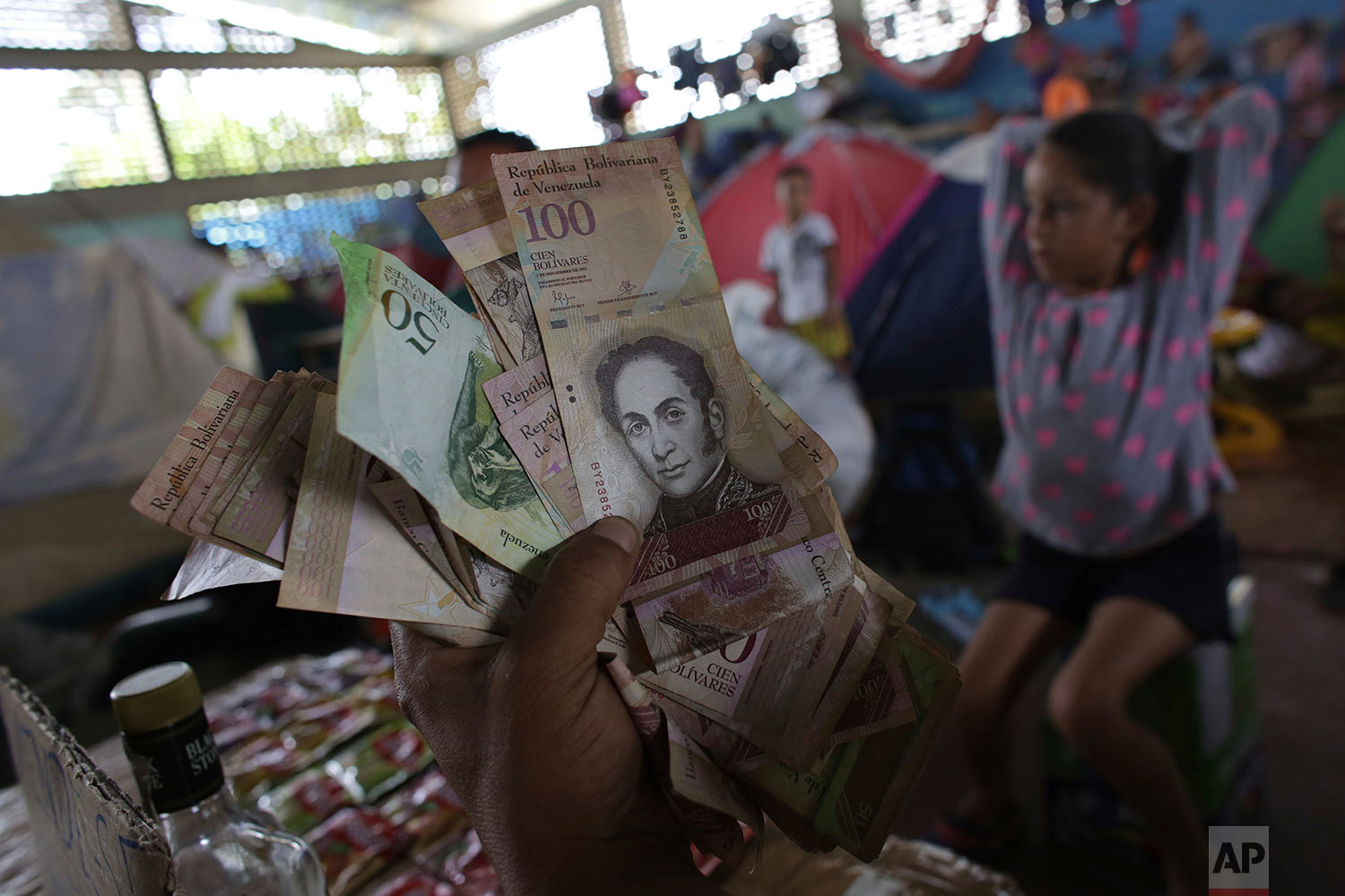 Venezuelan migrant Charlie Ivan Delgado shows his country's currency as he talks about the economic crisis at a migrant shelter that offers three meals a day where he brought his family of five, inside the Tancredo Neves Gymnasium in Boa Vista, Roraima state, Brazil, March 8, 2018. (AP Photo/Eraldo Peres)