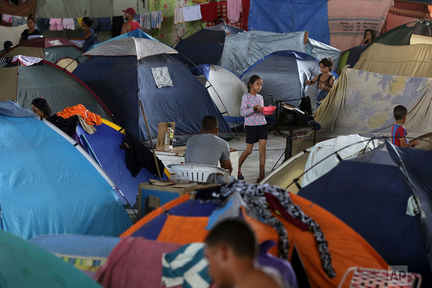 In this March 8, 2018 photo, tents fill the Tancredo Neves Gymnasium that is operating as a shelter for Venezuelans in Boa Vista, Roraima state, Brazil. (AP Photo/Eraldo Peres)