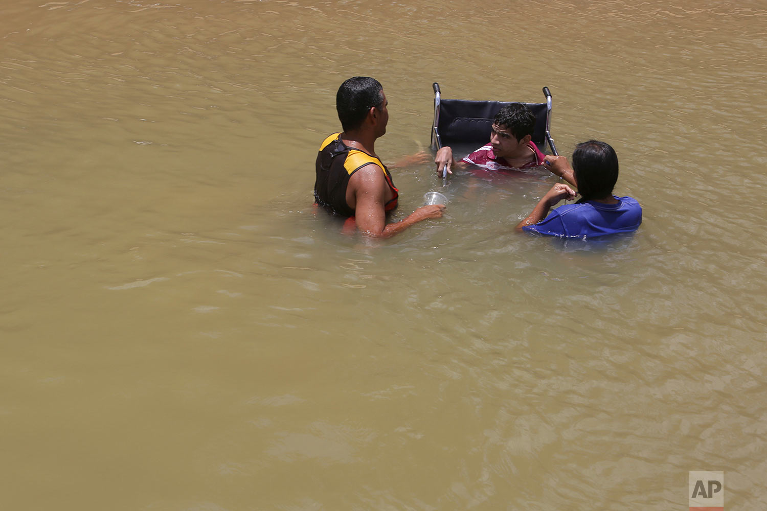 In this March 11, 2018 photo, a Venezuelan family, one in a wheelchair, cool off and bathe in the Branco River in Boa Vista, Roraima state, Brazil. (AP Photo/Eraldo Peres)