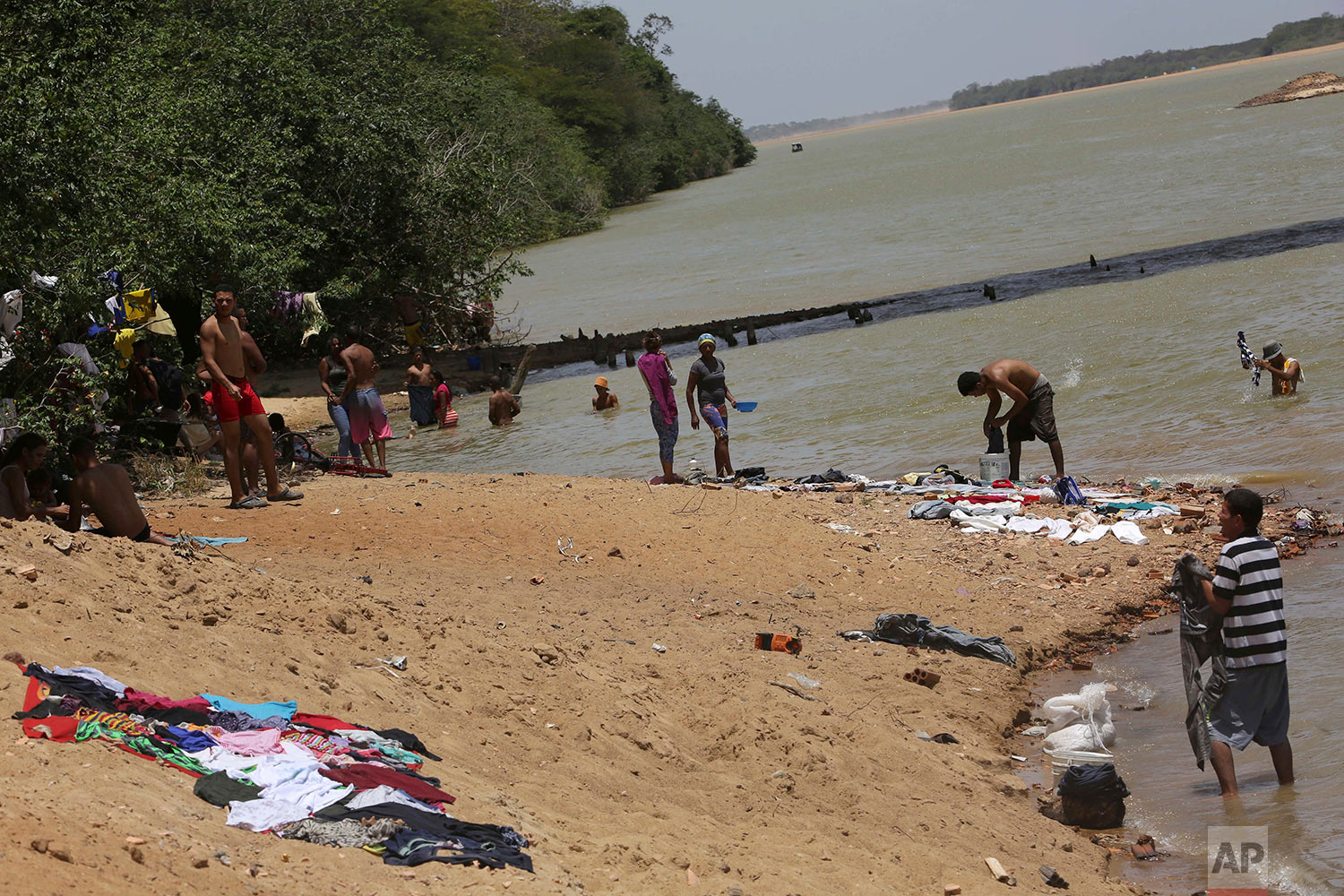 In this March 11, 2018 photo, Venezuelan migrants relax on the banks of the Branco River where they also wash clothes and bathe in Boa Vista, Roraima state, Brazil. (AP Photo/Eraldo Peres)