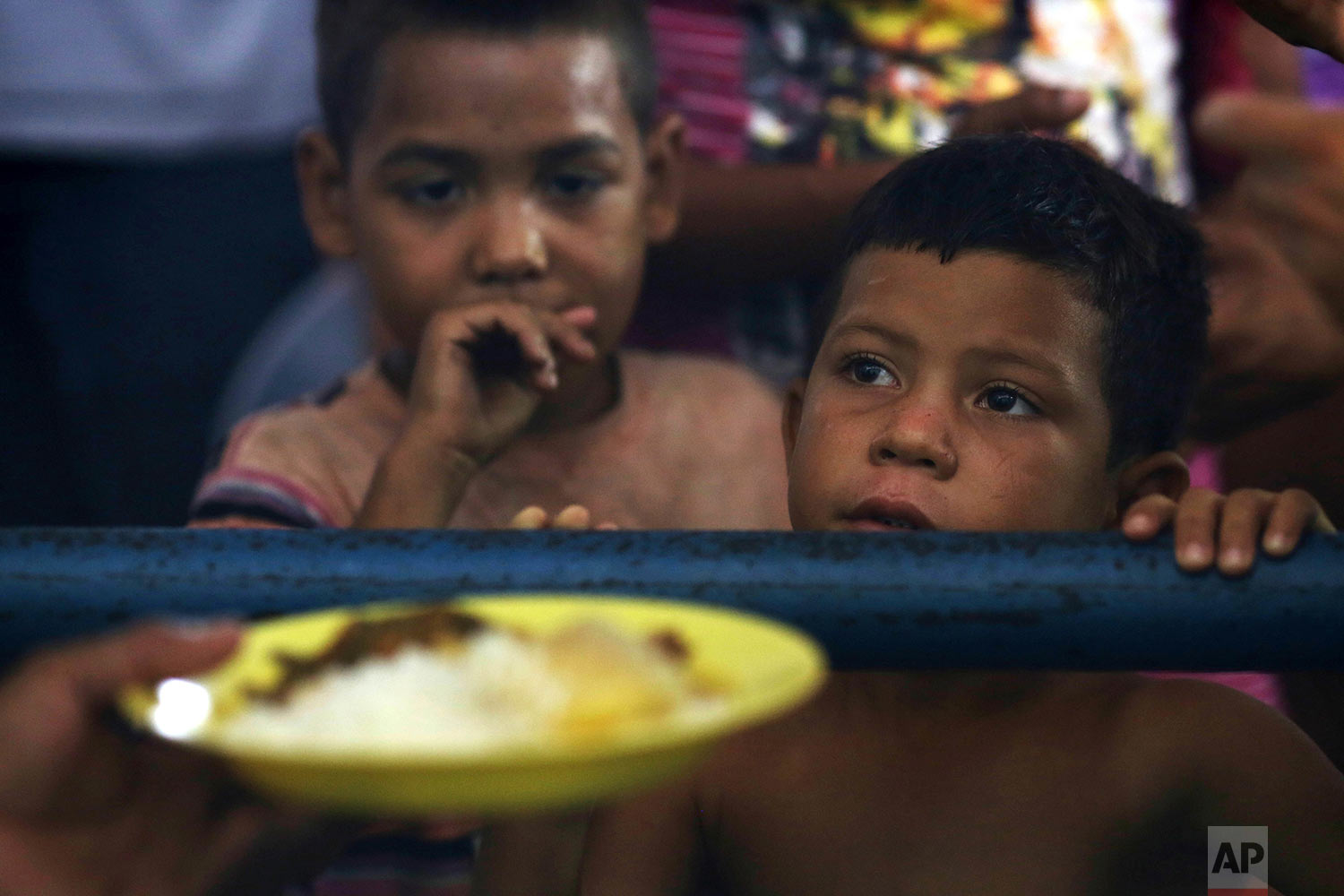 Venezuelan children wait for a free meal at a migrant shelter set up at the Tancredo Neves Gymnasium in Boa Vista, Roraima state, Brazil, March 8, 2018. (AP Photo/Eraldo Peres)