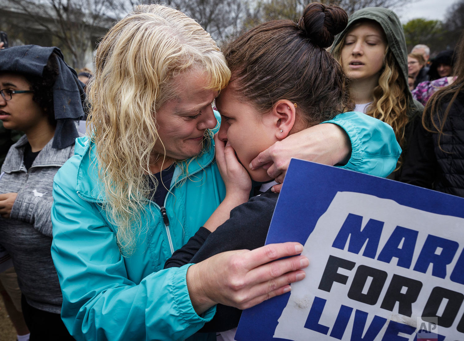 """Brenda Myers, center, comforts her daughter Jamie, who is an Ooltewah Middle School student, after a moment of silence at a """"March for Our Lives"""" rally in Coolidge Park on Saturday, March 24, 2018, in Chattanooga, Tenn. (Doug Strickland/Chattanooga Times Free Press via AP)"""
