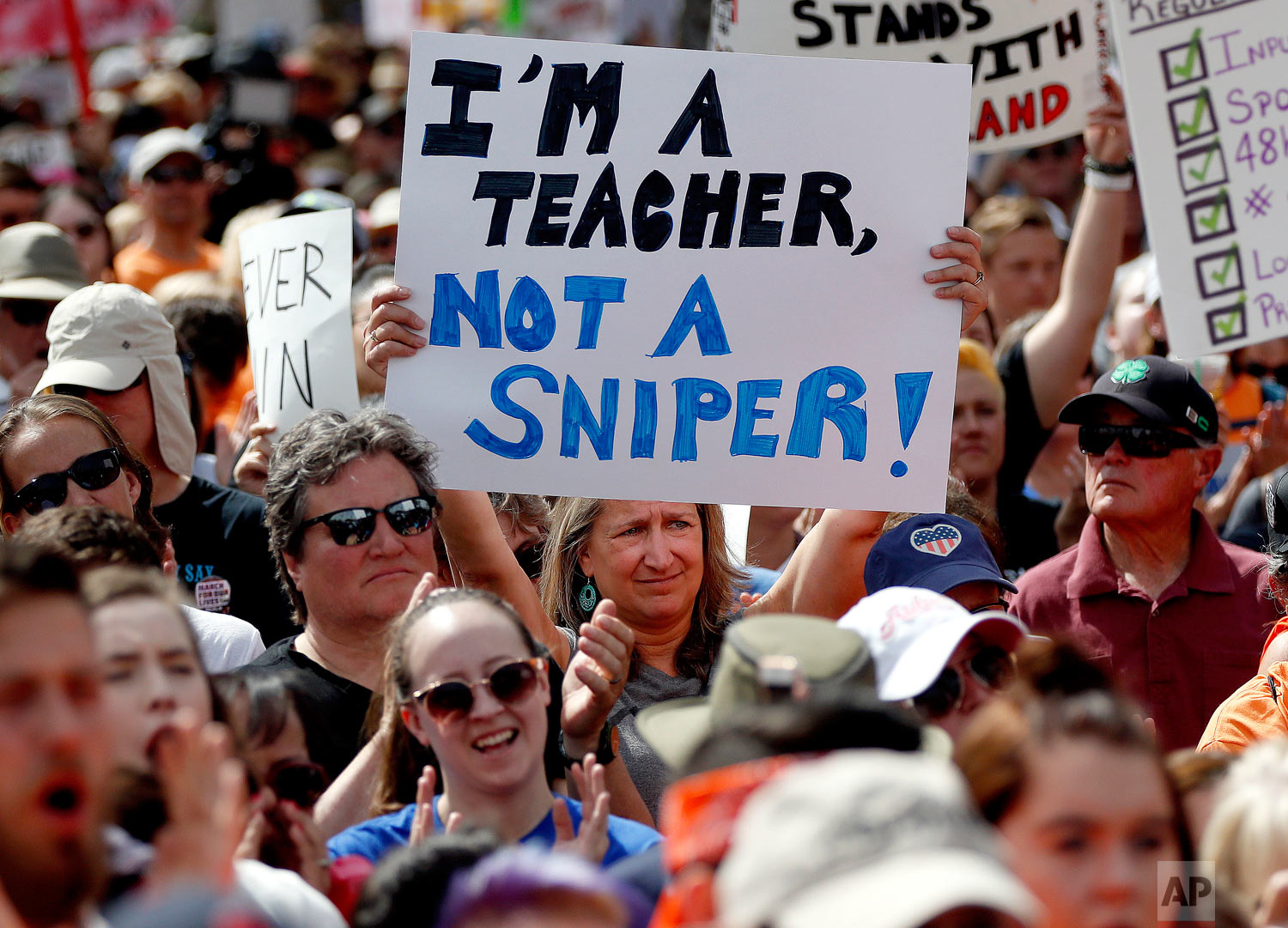 """People participate in a """"March For Our Lives"""" rally at the state Capitol, Saturday, March 24, 2018, in Phoenix. Students and activists across the country planned events Saturday in conjunction with a Washington march spearheaded by teens from Marjory Stoneman Douglas High School in Parkland, Fla., where over a dozen people were killed in February. (AP Photo/Matt York)"""