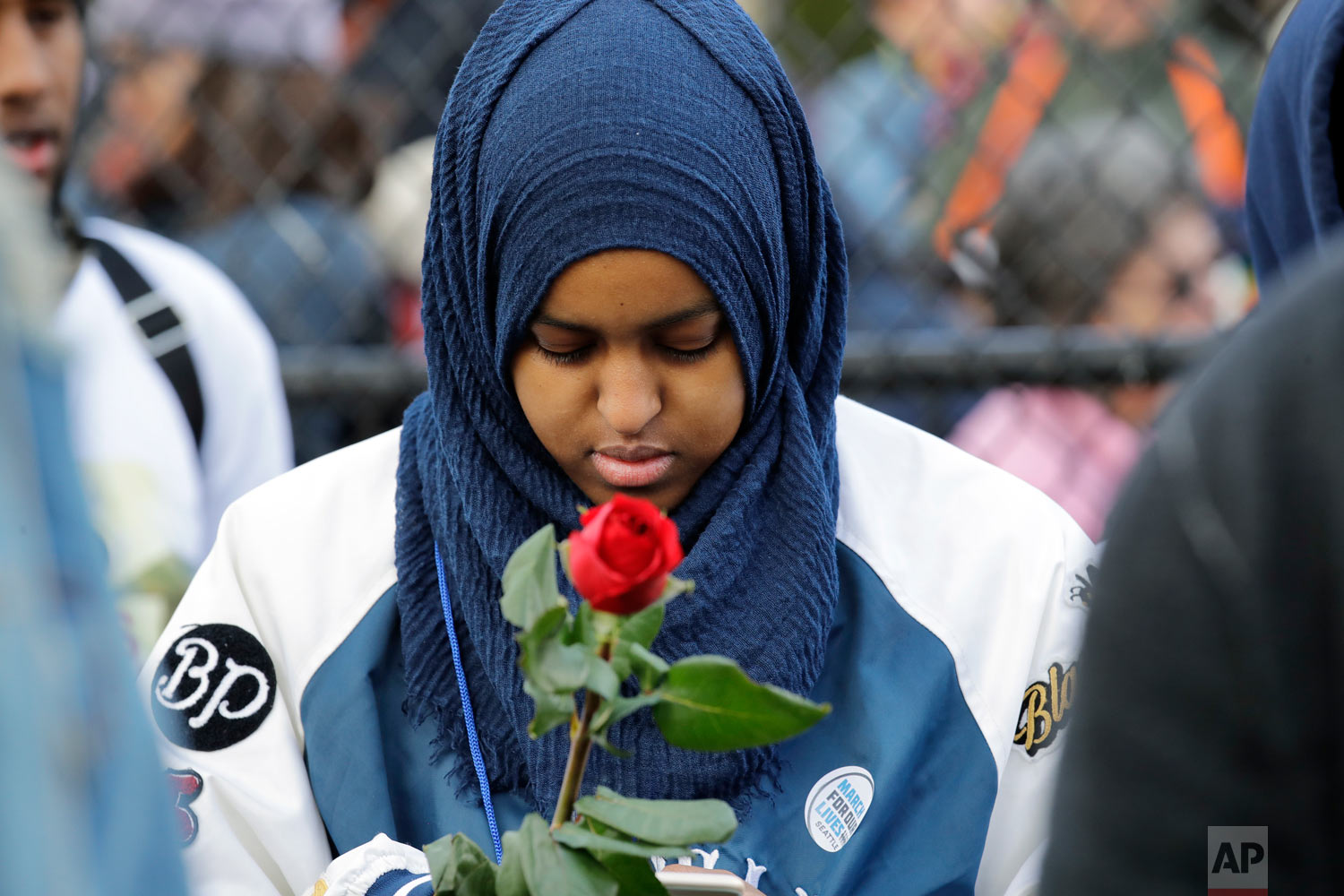 Naj Ali, a high school senior, holds a rose in memory of a person lost to gun violence during a rally before a march in favor of gun control Saturday, March 24, 2018, in Seattle.   Summoned to action by student survivors from Marjory Stoneman Douglas High School in Parkland, Fla., hundreds of thousands of teenagers and their supporters rallied in the nation's capital and cities across the U.S. on Saturday to press for gun control. (AP Photo/Elaine Thompson)