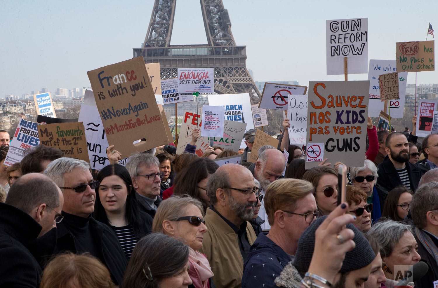 """People hold banners during the """"March For Our Lives"""" event in Paris, France, Saturday, March 24, 2018. The march is one of hundreds happening across the U.S. and the world to urge U.S. lawmakers to pass stricter gun safety legislation after deadly school shootings. (AP Photo/Michel Euler)"""