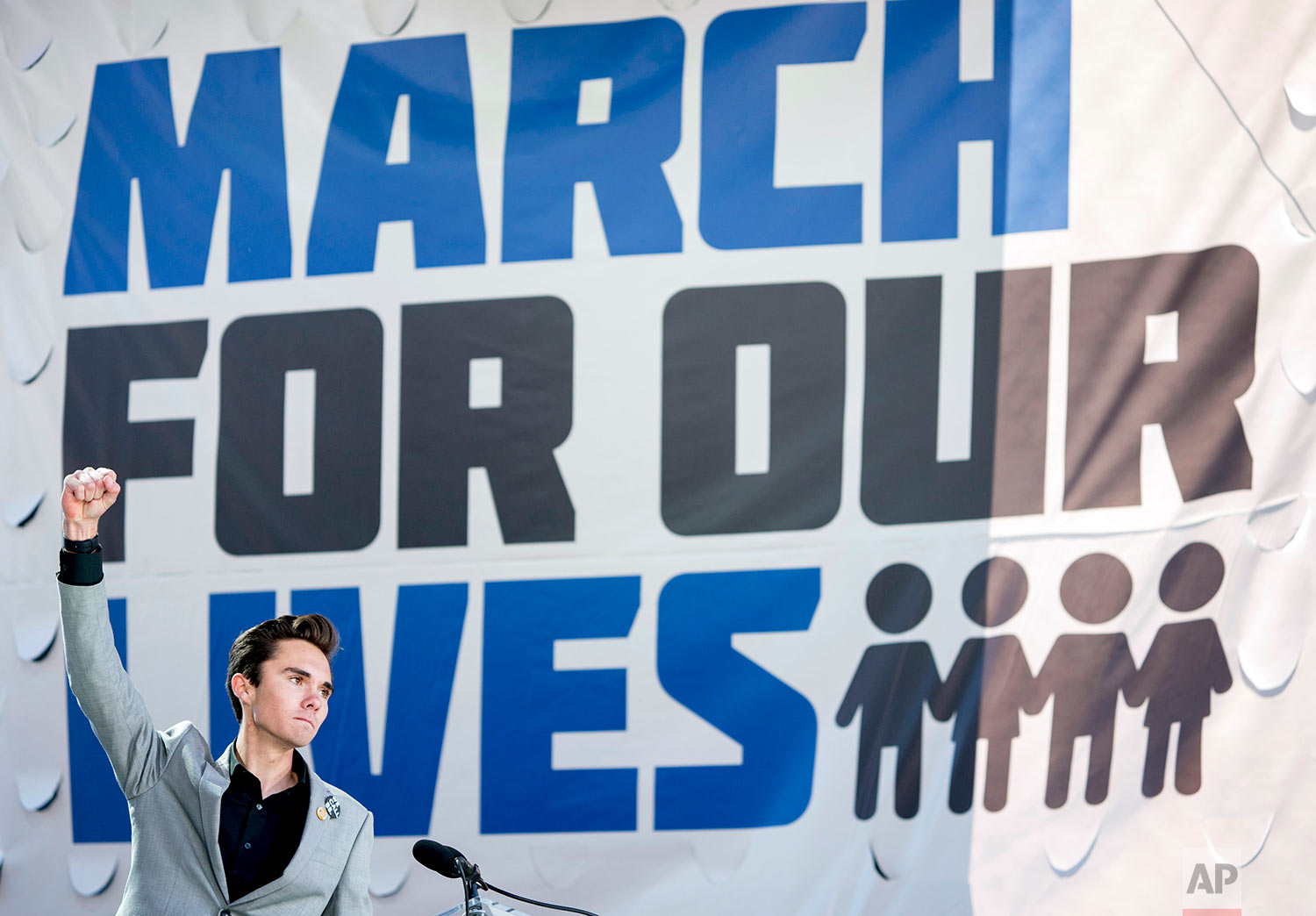 """David Hogg, a survivor of the mass shooting at Marjory Stoneman Douglas High School in Parkland, Fla., raises his fist after speaking during the """"March for Our Lives"""" rally in support of gun control in Washington, Saturday, March 24, 2018. (AP Photo/Andrew Harnik)"""