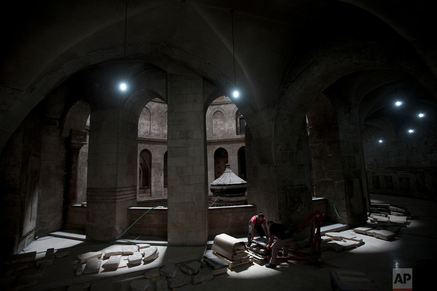 In this Friday, Oct. 7, 2016 photo, members of the conservation team lift a stone to clean and digitally scan before reinstalling it on the faÁade of the Edicule, the shrine that houses what is believed to be the tomb of Jesus in the Church of the Holy Sepulchre in Jerusalem's Old City. (AP Photo/Oded Balilty)