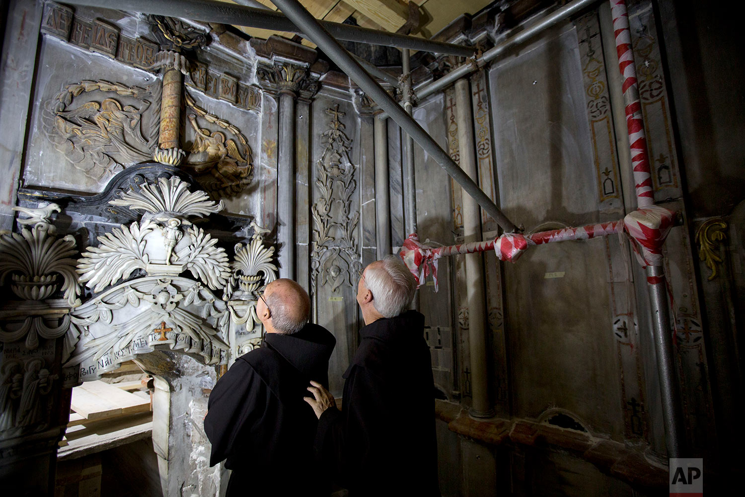 In this Friday, Oct. 28, 2016 photo, Franciscan priests visit the Tomb of Jesus during its renovation in the Church of the Holy Sepulchre in Jerusalem's Old City.  (AP Photo/Oded Balilty)