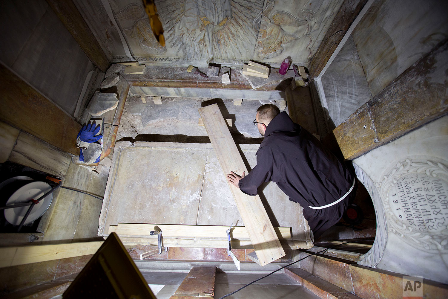 A priest looks at Jesus' tomb in the Church of the Holy Sepulchre in Jerusalem's old city in Jerusalem, Israel,  Thursday, Oct. 27, 2016. (AP Photo/Oded Balilty)