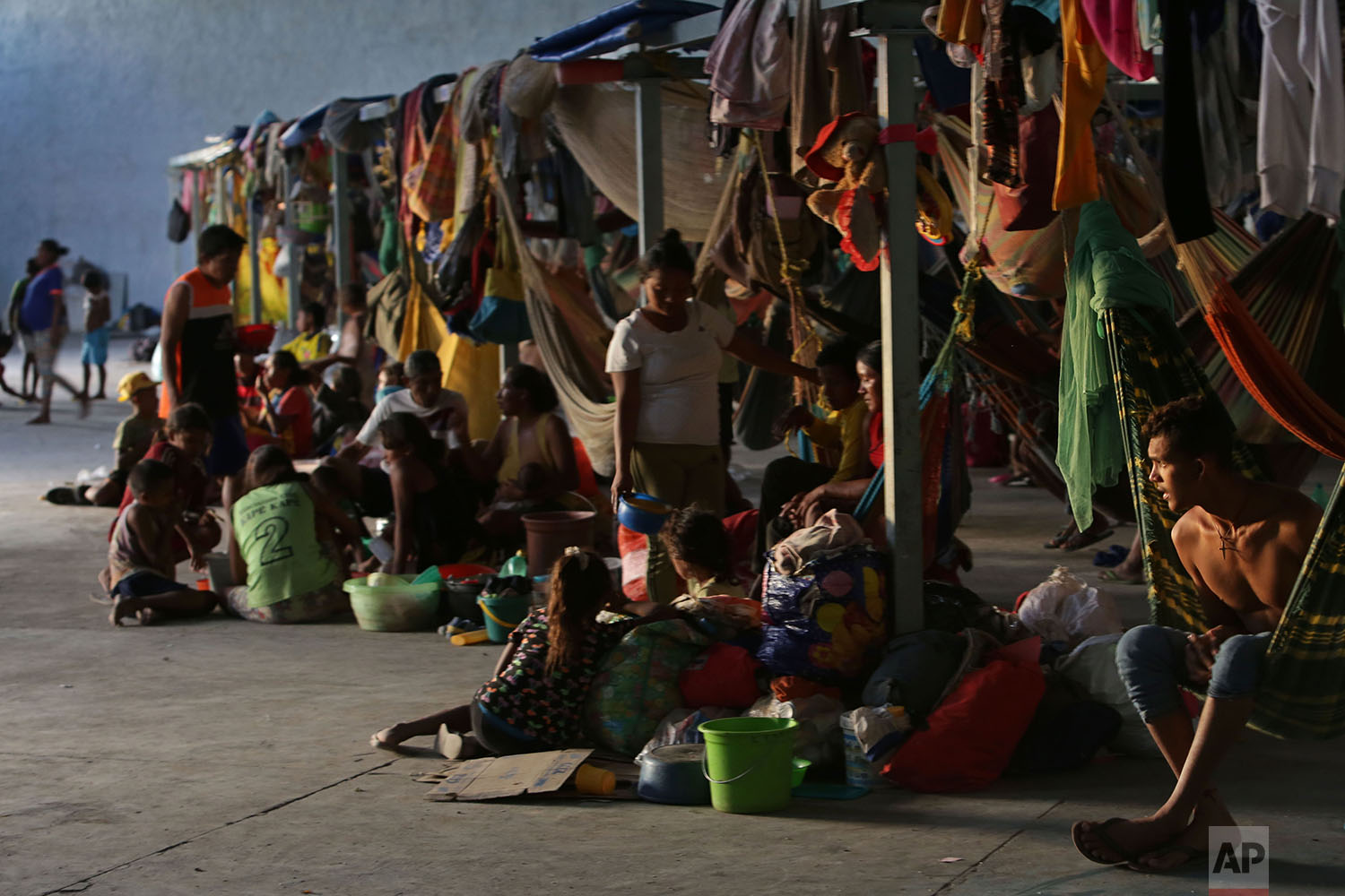 In this March 10, 2018 photo, a Warao refugee looks out from his hammock next to families sitting on the floor at a shelter, in Pacaraima, Brazil. (AP Photo/Eraldo Peres)