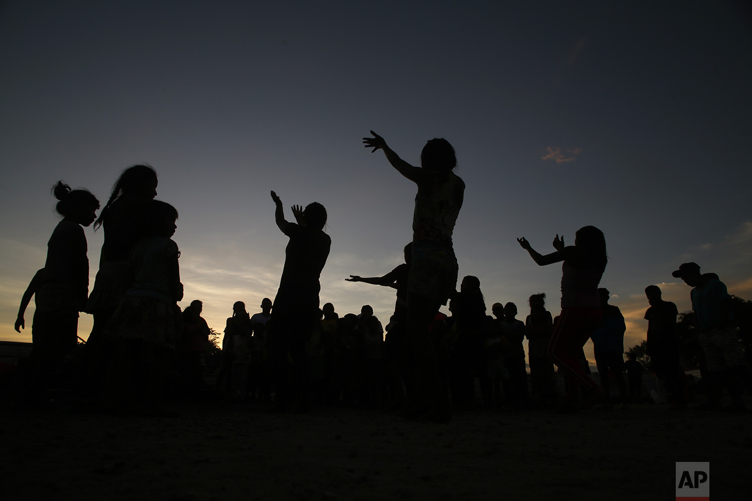 In this March 10, 2018 photo, Warao women dance in the outdoor area of a shelter, in Pacaraima, Brazil. (AP Photo/Eraldo Peres)