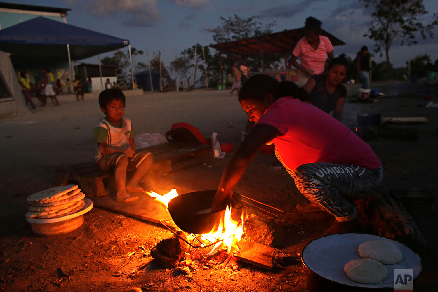 In this March 10, 2018 photo, a Warao woman from Venezuela, cooks bread over a fire in the outdoor area of a shelter, in Pacaraima, Brazil. (AP Photo/Eraldo Peres)