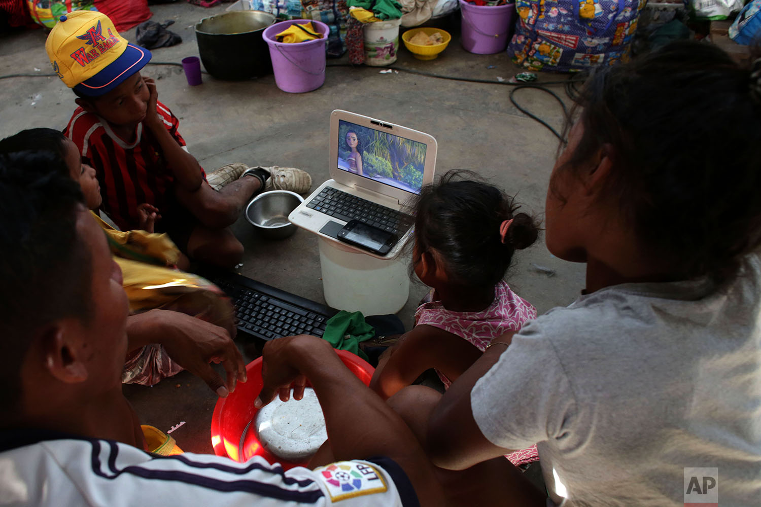 In this March 10, 2018 photo, Warao children from Venezuela watch cartoons on a computer laptop in a shelter, in Pacaraima, Brazil. (AP Photo/Eraldo Peres)