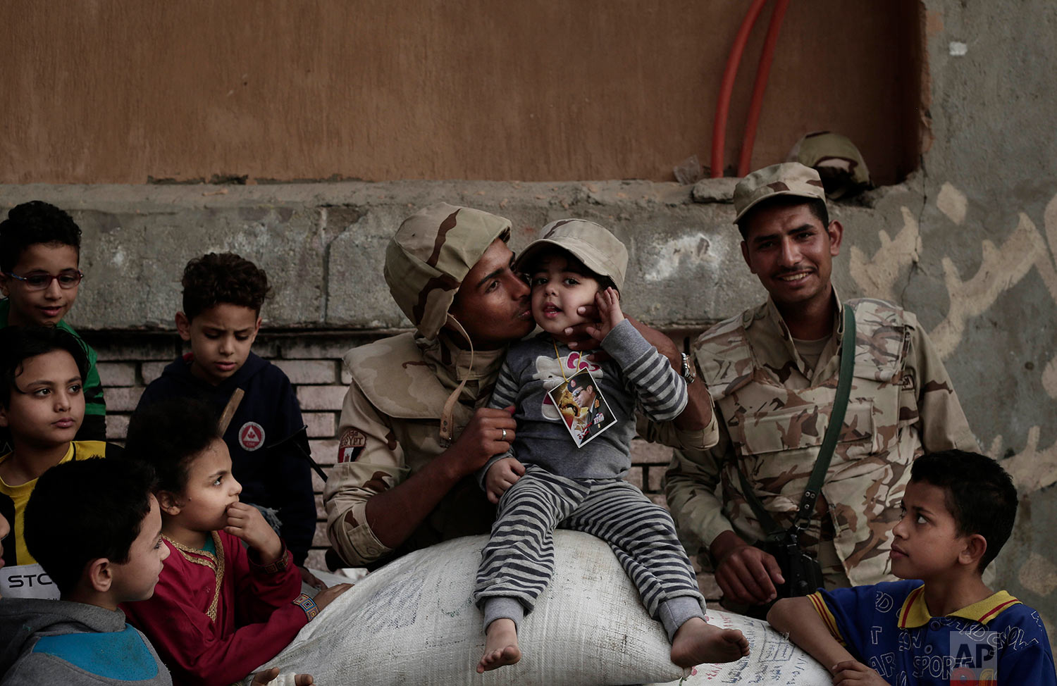 A military solider guarding a polling station kisses a girl during the first day of voting in the presidential election in the village of Kerdasa, Giza, Egypt, Monday, March 26, 2018. Polls opened on Monday in Egypt's presidential election with the outcome — a second, four-year term for President Abdel-Fattah el-Sissi — a foregone conclusion, in what is seen by critics as a signal of the country's return to the authoritarian rule that prevailed since the 1950s. (AP Photo/Nariman El-Mofty)