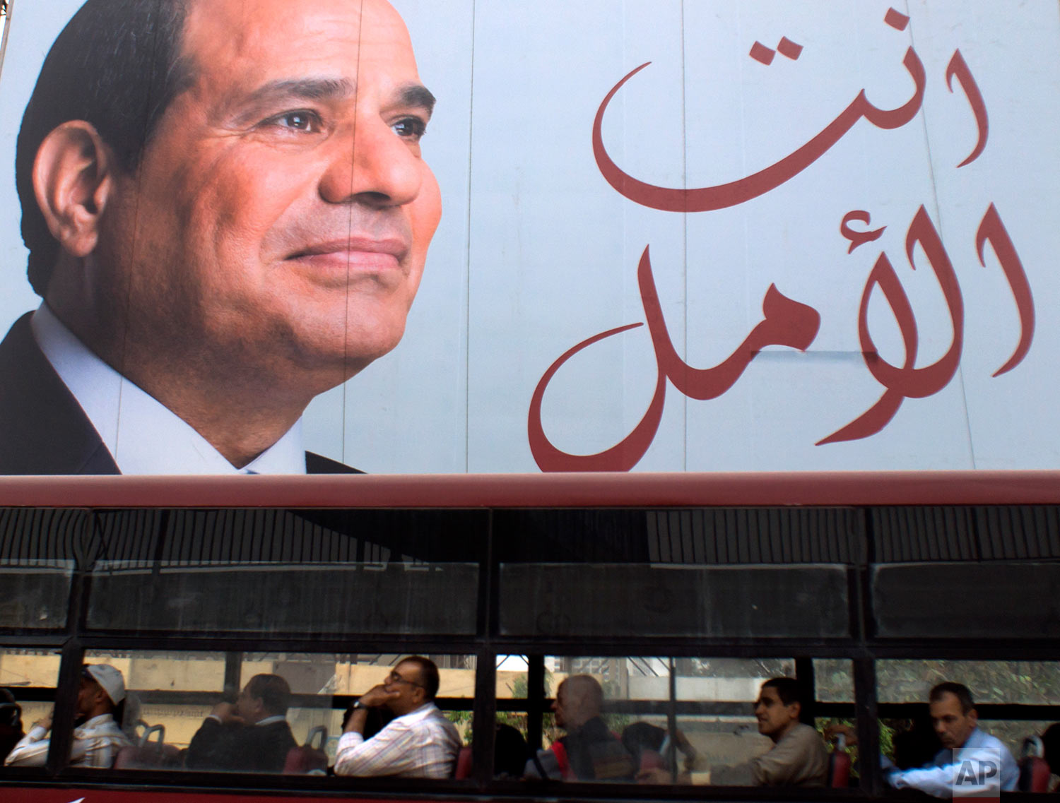 """People travel on a public bus under an election banner for Egyptian President Abdel-Fattah el-Sissi with Arabic that reads, """"you are the hope,"""" in Cairo, Egypt, Wednesday, March 28, 2018. (AP Photo/Amr Nabil)"""