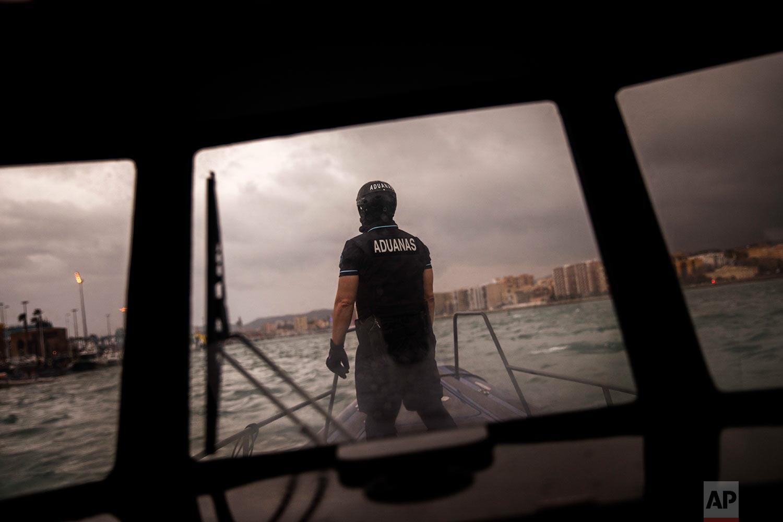 In this Wednesday, Feb. 28, 2018 photo, Spain's Customs Surveillance Service officer sails near the port of Algeciras, in Cadiz province, south of Spain. (AP Photo/Emilio Morenatti)