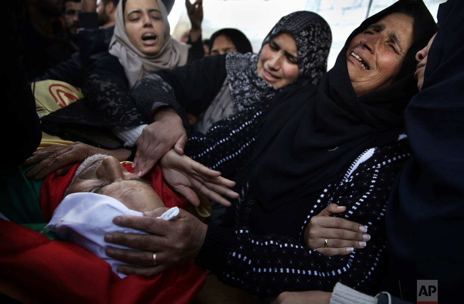 Relatives of Palestinian 59-year-old farmer, Muhammed Abu Jamaa, mourn over his body in the family house during his funeral in town of Khan Younis, southern Gaza Strip, Sunday, March 4, 2018. (AP Photo/ Khalil Hamra)