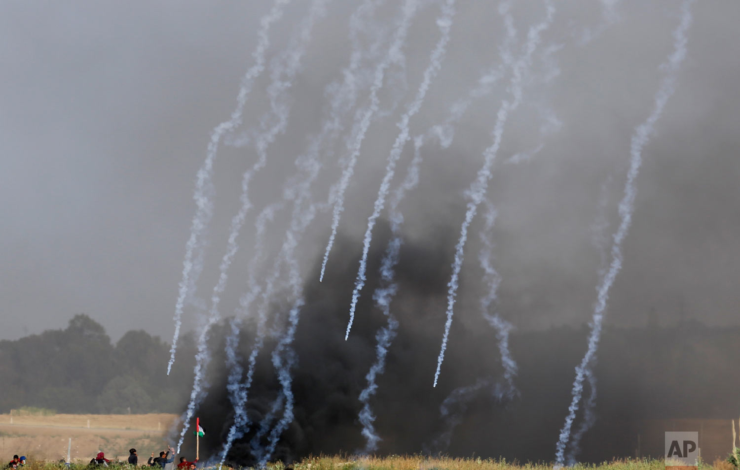 Teargas canisters fired by Israeli troops falls down at Palestinians during a demonstration near the Gaza Strip border with Israel, in eastern Gaza City, Friday, March 30, 2018.(AP Photo/Hatem Moussa)