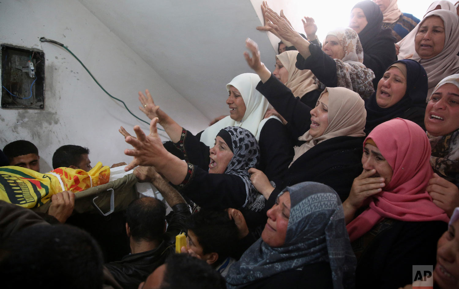 """Relatives mourn over the body of Hamdan Abu Amsha, 23, during his funeral at the family house in Beit Hanoun, Gaza Strip, Saturday, March 31, 2018. Israel will target """"terror organizations"""" in Gaza if violence along the territory's border with Israel drags on, the chief military spokesman warned Saturday, a day after thousands of Palestinians staged protests near the border fence. (AP Photo/Adel Hana)"""