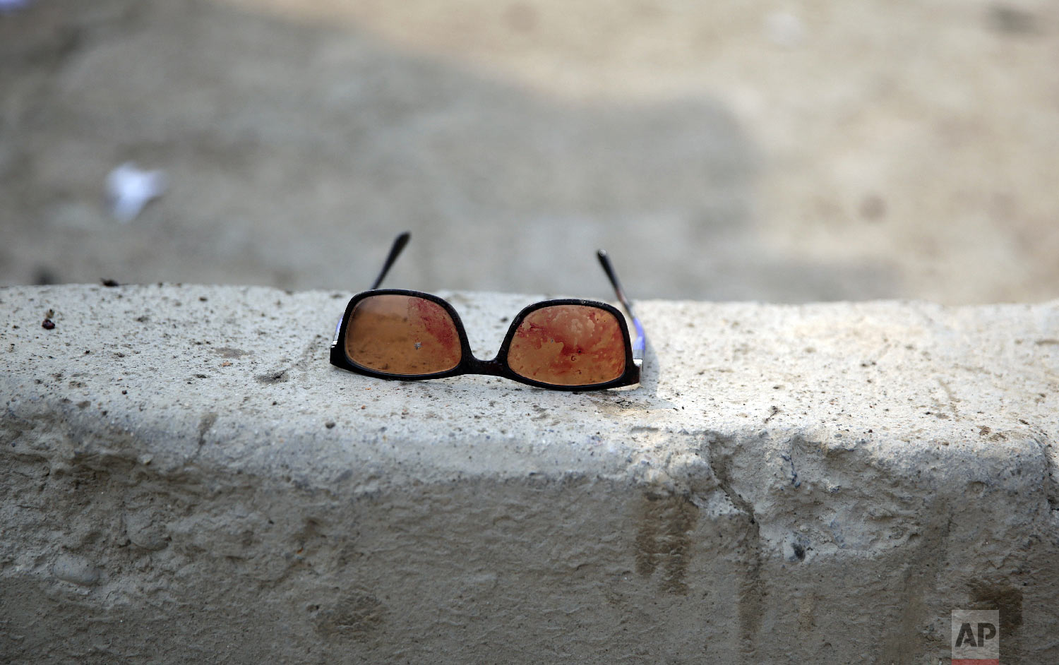 Sunglasses covered in blood are left at the site of a suicide attack in Kabul, Friday, March 9, 2018.(AP Photo/Massoud Hossaini)