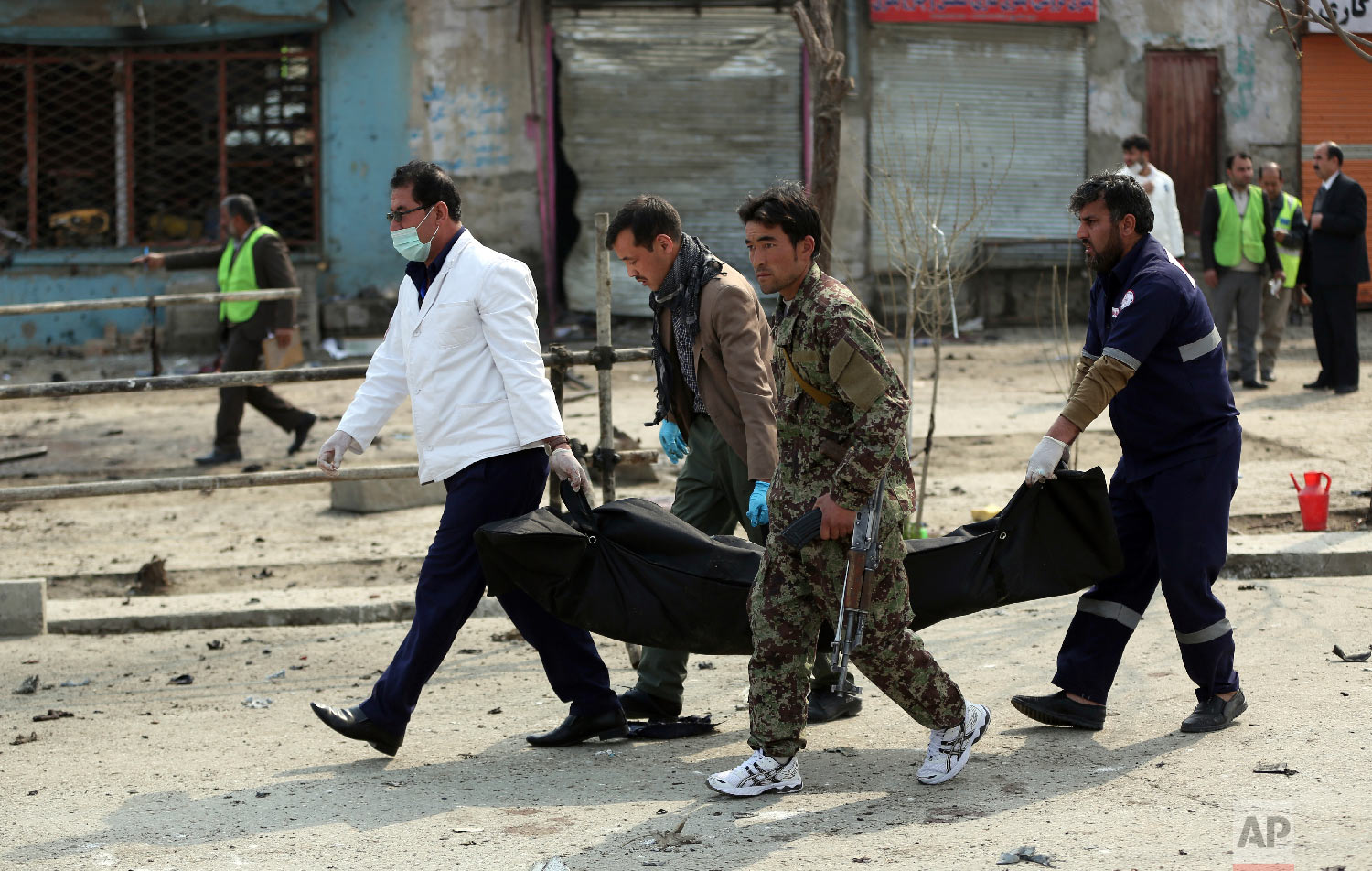Security personnel carry a body at the site of a suicide attack in Kabul, Friday, March 9, 2018. (AP Photo/Massoud Hossaini)