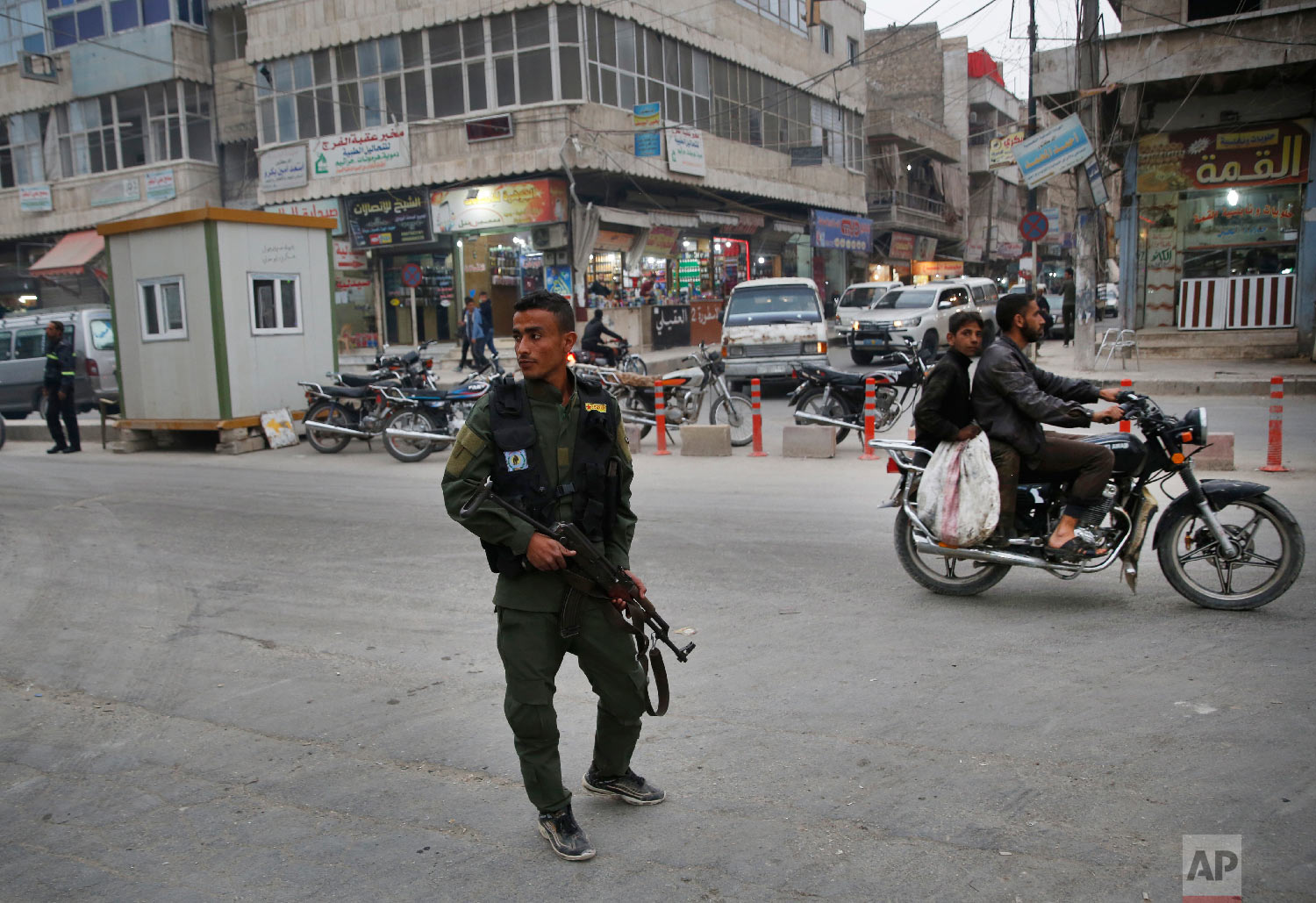 In this photo taken on Wednesday, March 28, 2018, a member of the Kurdish internal security forces patrols a commercial street in Manbij, north Syria. (AP Photo/Hussein Malla)