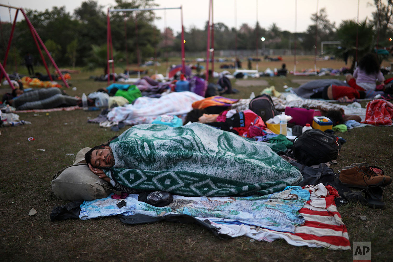 Central American migrants traveling with the Migrants Stations of the Cross caravan sleep at a sports club in Matias Romero, Oaxaca State, Mexico, early Tuesday, April 3, 2018. (AP Photo/Felix Marquez)