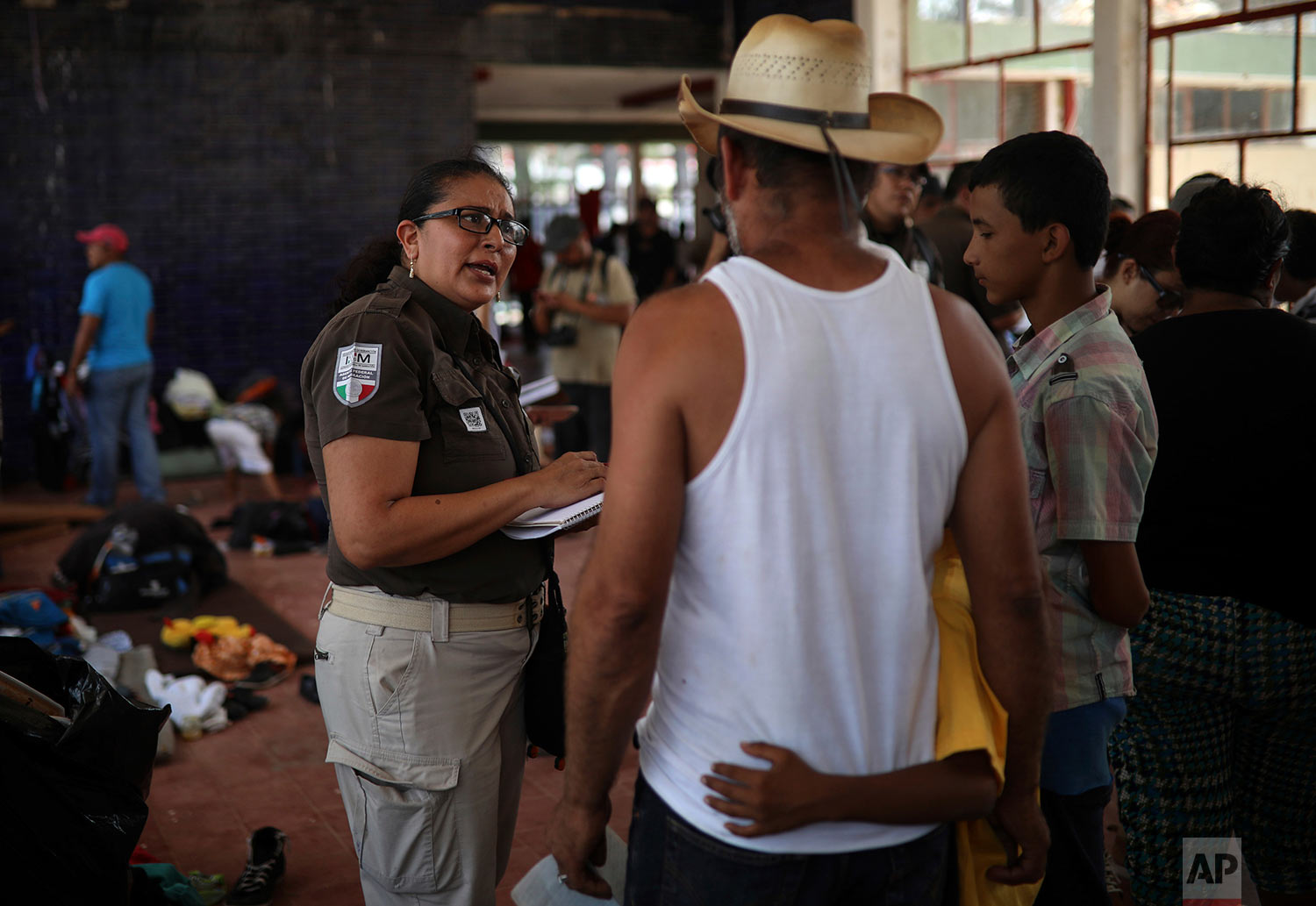 A Mexican immigration official attends a Honduran family participating in the Migrant Stations of the Cross caravan that's making a stop at a sports club in Matias Romero, Oaxaca State, Mexico, Tuesday, April 3, 2018. (AP Photo/Felix Marquez)