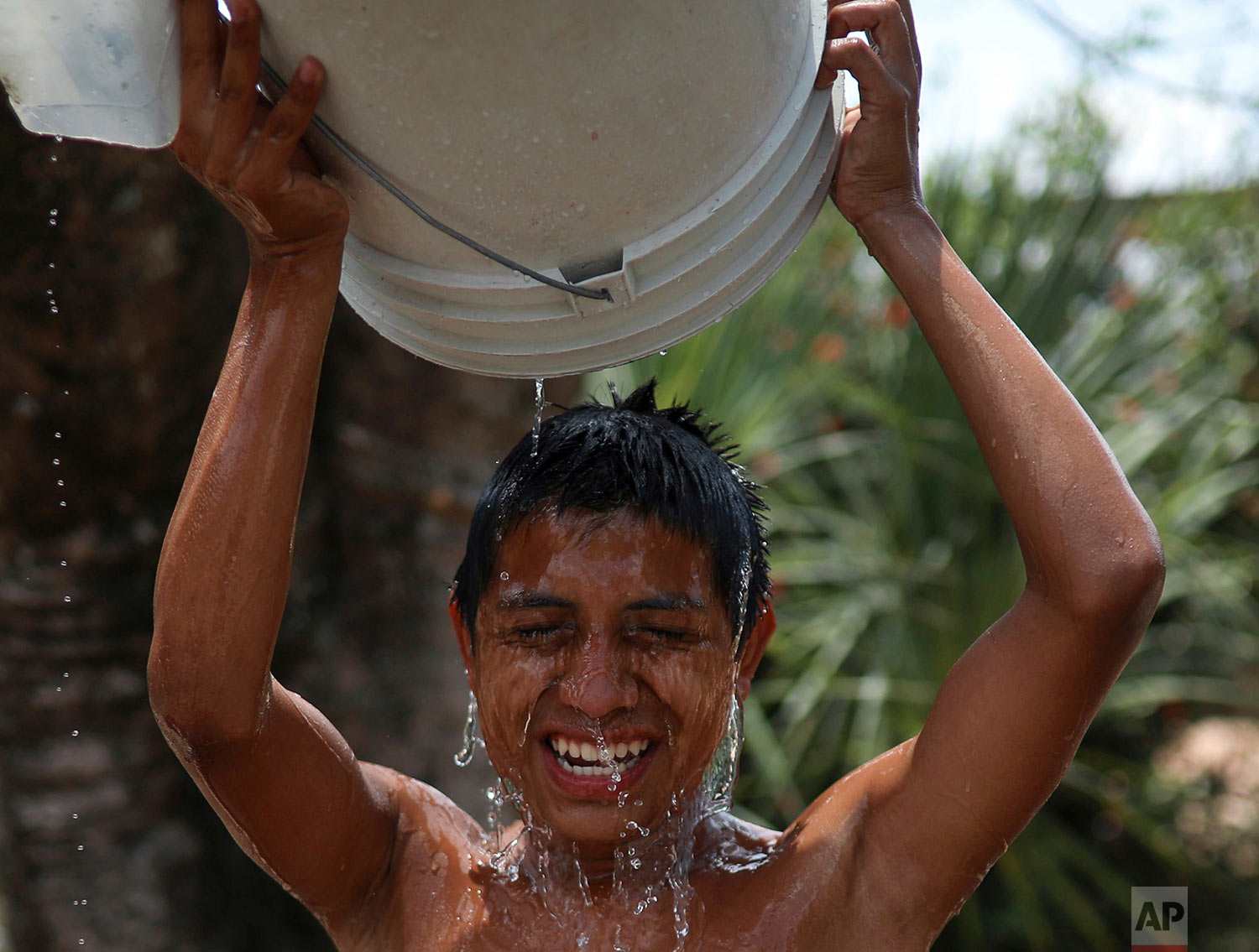 A Central American migrant participating in the Migrant Stations of the Cross caravan takes a bucket bath during the caravan's stop at a sports club in Matias Romero, Oaxaca State, Mexico, Tuesday, April 3, 2018. (AP Photo/Felix Marquez)