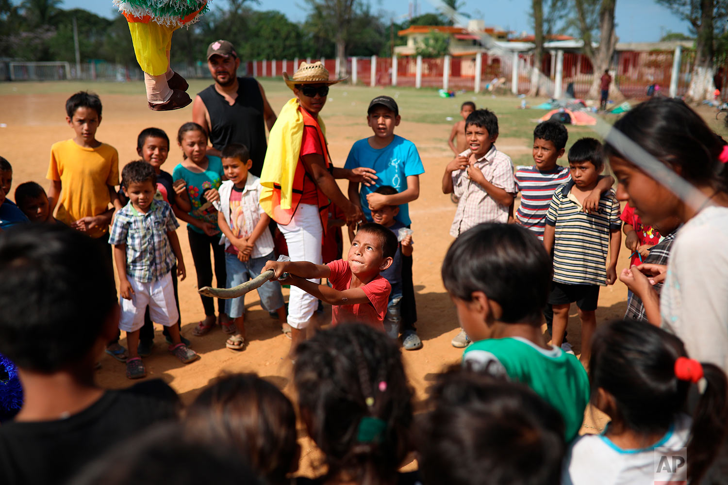 Central American migrant children play with a piñata during the annual Migrant Stations of the Cross caravan as the caravan stops at a sports center in Matias Romero, Oaxaca state, Mexico, Monday, April 2, 2018. (AP Photo/Felix Marquez)