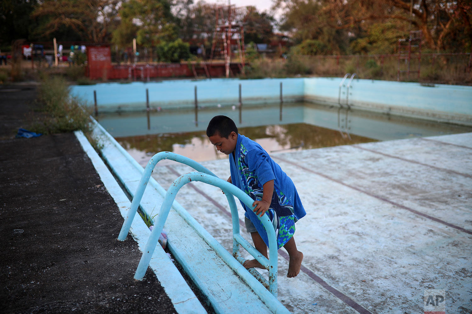 A child plays in an abandoned pool as the adults sleep at a sports club where Central American migrants traveling with the annual Migrants Stations of the Cross caravan are camped out in Matias Romero, Oaxaca State, Mexico, Tuesday, April 3, 2018. (AP Photo/Felix Marquez)