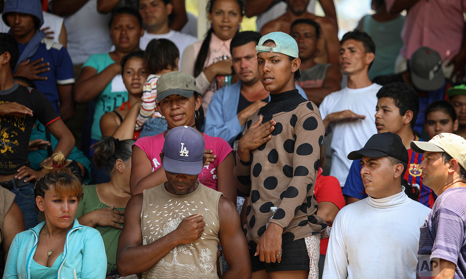 Central American migrants from Honduras sing their national anthem during the annual Migrant Stations of the Cross caravan as the group makes a stop in Matias Romero, Oaxaca state, Mexico, Monday, April 2, 2018. (AP Photo/Felix Marquez)