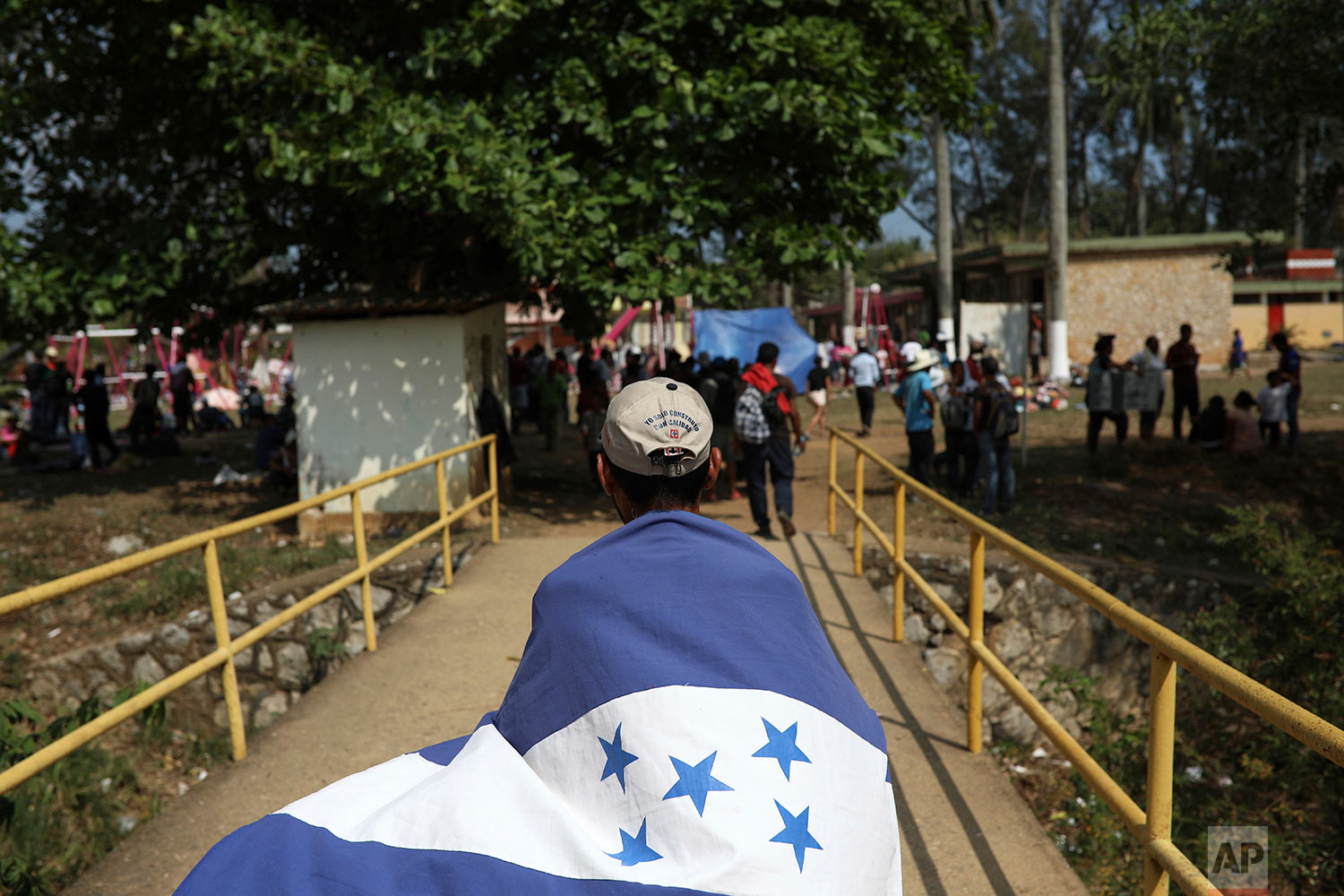A Central American migrant from Honduras wears his nation's flag during the annual Migrant Stations of the Cross caravan as the group makes a stop in Matias Romero, Oaxaca state, Mexico, Monday, April 2, 2018. (AP Photo/Felix Marquez)