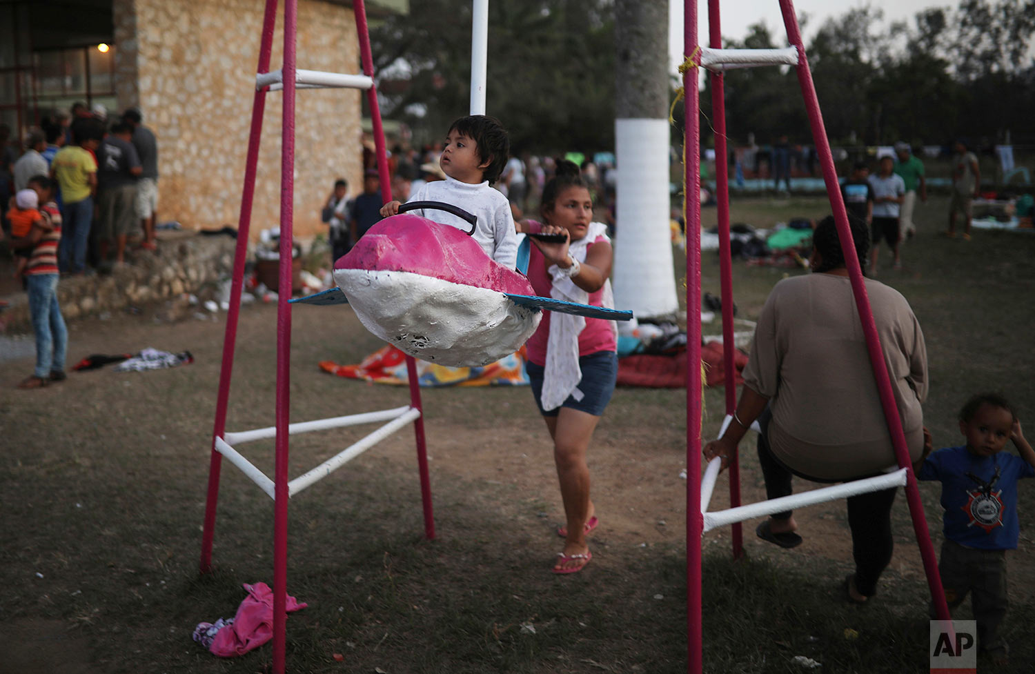 Central American migrant families participating in the Migrant Stations of the Cross caravan play on a swing during the caravan's stop at a sports center in Matias Romero, Oaxaca state, Mexico, late Monday, April 2, 2018. (AP Photo/Felix Marquez)