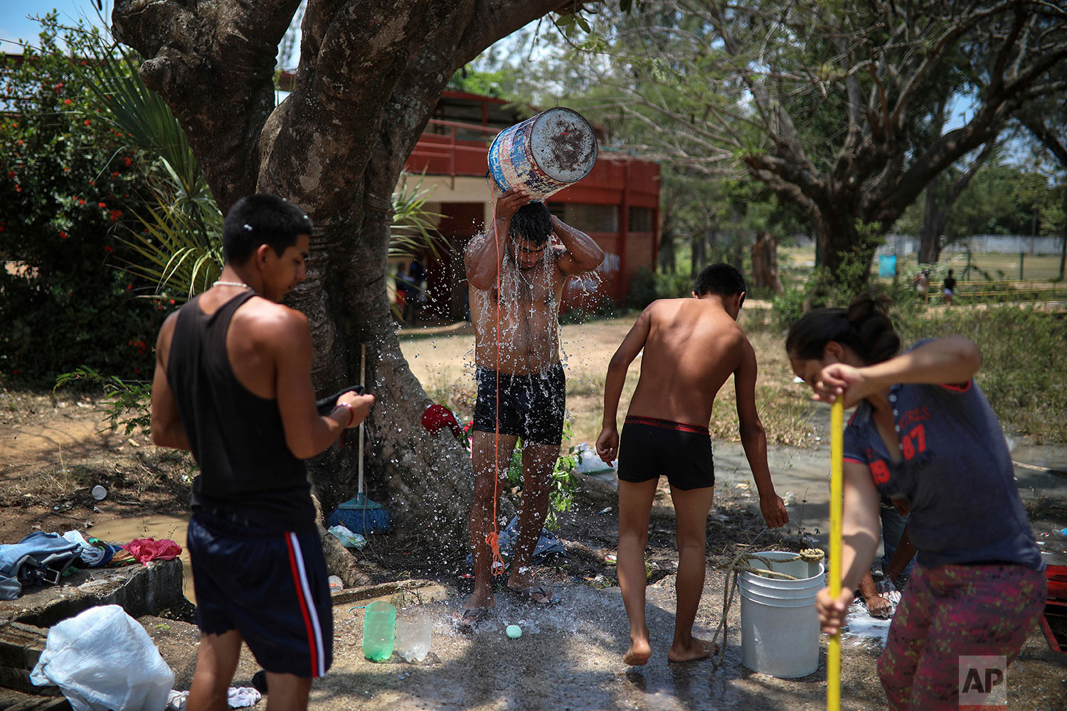 Central American migrants participating in the Migrant Stations of the Cross caravan take bucket baths where the group set up camp at a sports club in Matias Romero, Oaxaca State, Mexico, Tuesday, April 3, 2018. (AP Photo/Felix Marquez)