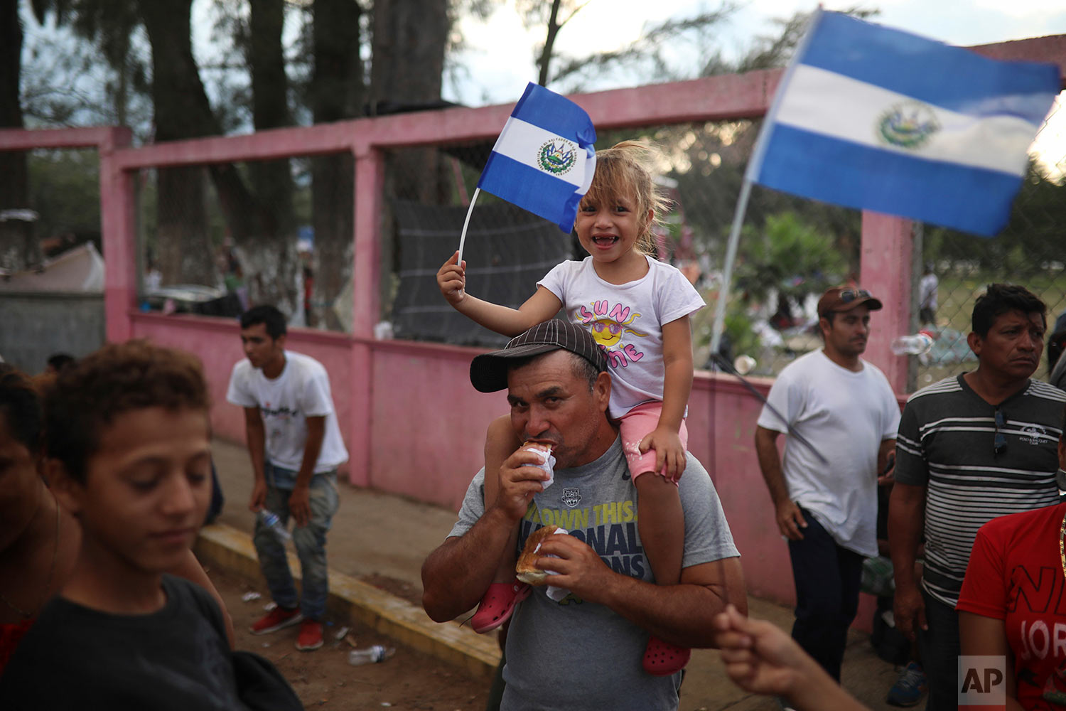 A Salvadoran girl waves her national flag as Central American migrants traveling with the annual Stations of the Cross caravan march to call for migrants' rights and protest the policies of U.S. President Donald Trump and Honduran President Juan Orlando Hernandez, in Matias Romero, Oaxaca state, Mexico, Tuesday, April 3, 2018.(AP Photo/Felix Marquez)