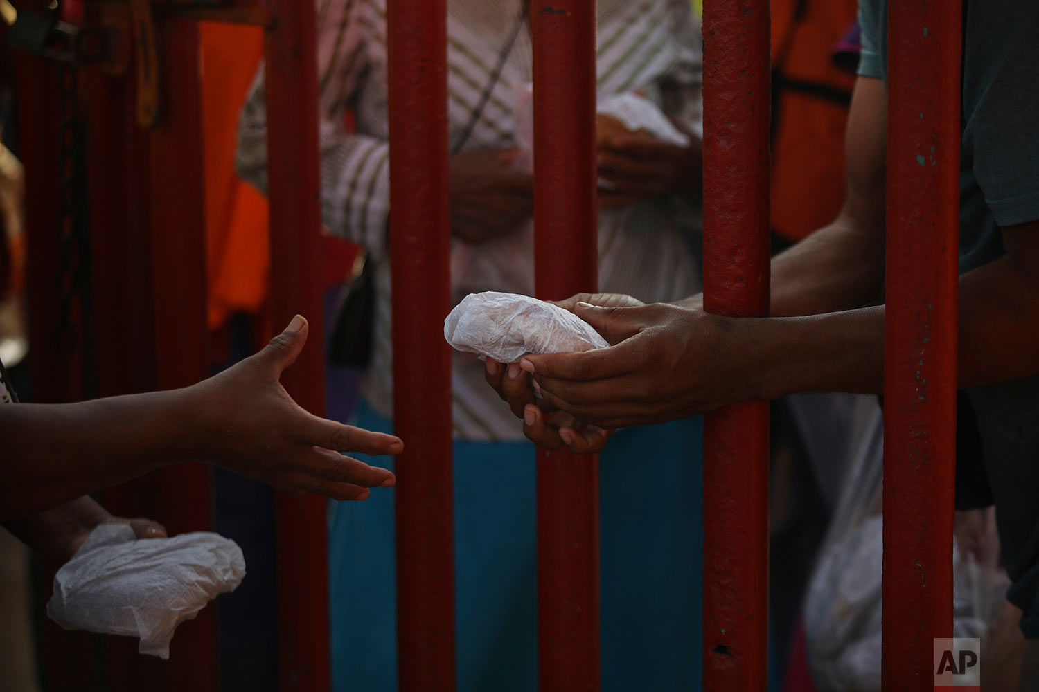 Volunteers pass sandwiches through a fence to Central American migrants traveling with the annual Stations of the Cross caravan as they camp out at a sports club in Matias Romero, Oaxaca state, Mexico, Tuesday, April 3, 2018. (AP Photo/Felix Marquez)