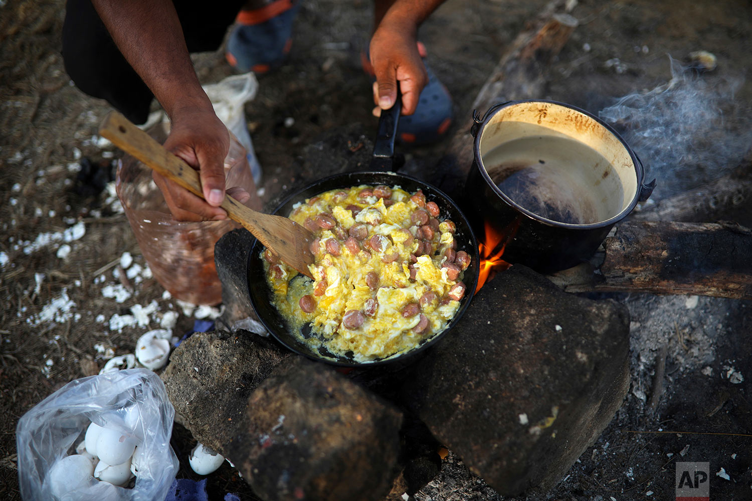 Elmer Zelaya of El Salvador prepares a breakfast of eggs and sausage for his family of five, at the sports club where Central American migrants traveling with the annual Stations of the Cross caravan are camped out in Matias Romero, Oaxaca State, Mexico, Wednesday, April 4, 2018. (AP Photo/Felix Marquez)