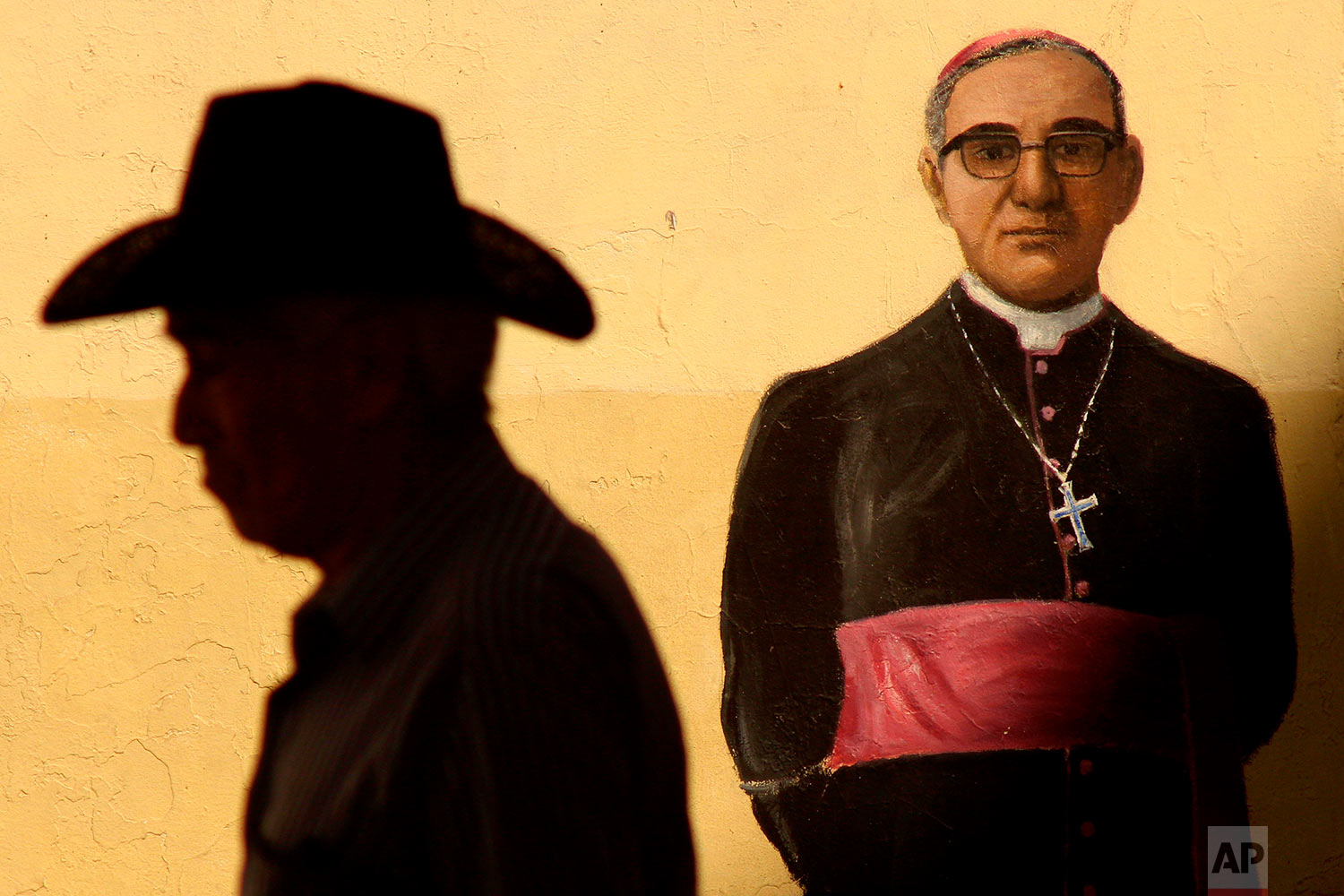 A man walks past a mural of late Archbishop Oscar Arnulfo Romero outside the Metropolitan Cathedral where Mass was offered to mark the 38th anniversary of the archbishop's death, in San Salvador, El Salvador, March 24, 2018. Pope Francis declared earlier this month that the churchman who became a hero for standing up for the poor and oppressed should be canonized along with the reformer Pope Paul VI. (AP Photo/Salvador Melendez)