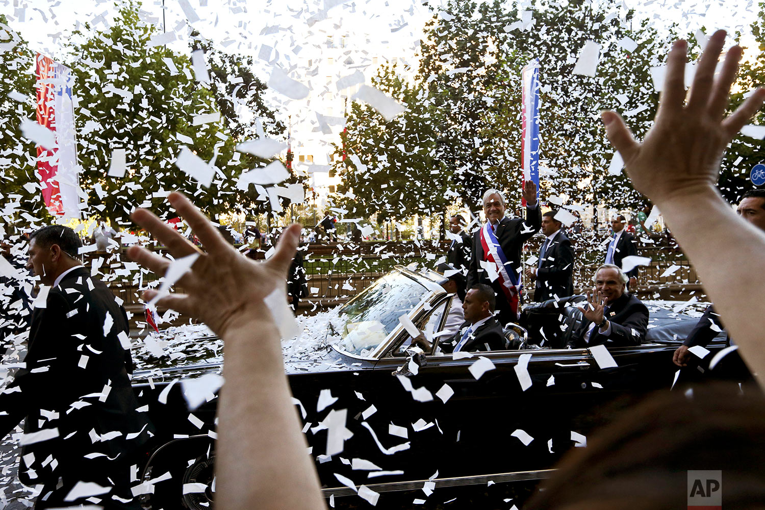 Chile's President Sebastian Pinera waves from under a shower of confetti as he makes his way to La Moneda presidential palace on the day of his inauguration in Santiago, Chile, March 11, 2018. Pinera returned to Chile's presidency, after his first term from 2010 to 2014. (AP Photo/Esteban Felix)