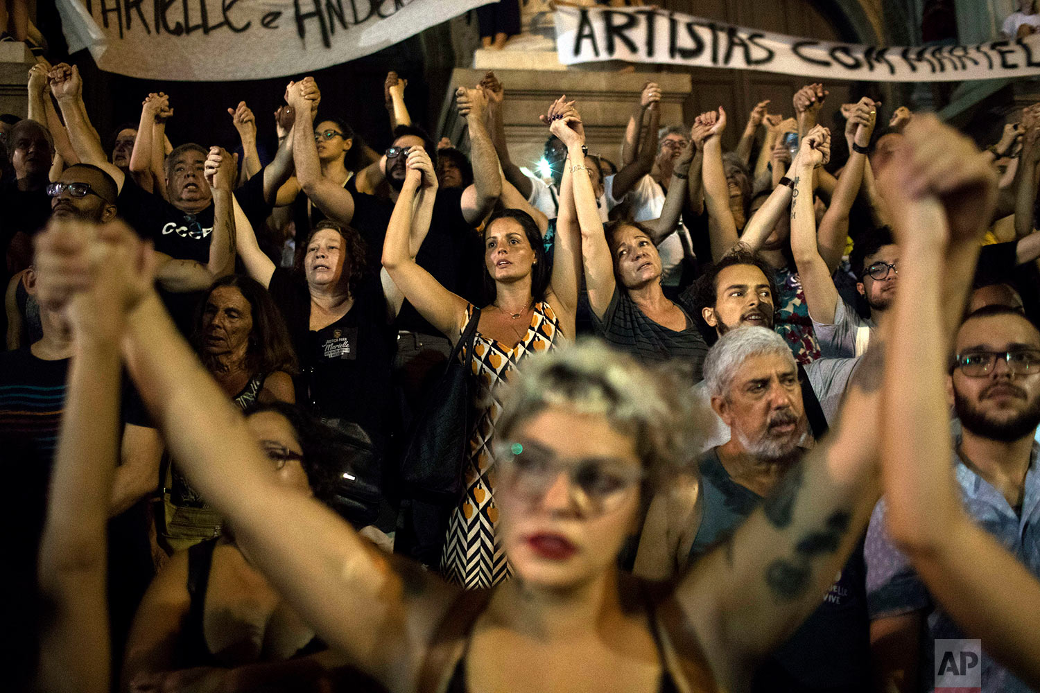 Women hold hands during continued protests against the murder of councilwoman and human rights activist Marielle Franco in Rio de Janeiro, Brazil, March 20, 2018. Franco and her driver, Anderson Pedro Gomes, were shot dead by assailants while returning from an event focused on empowering young black women. (AP Photo/Leo Correa)