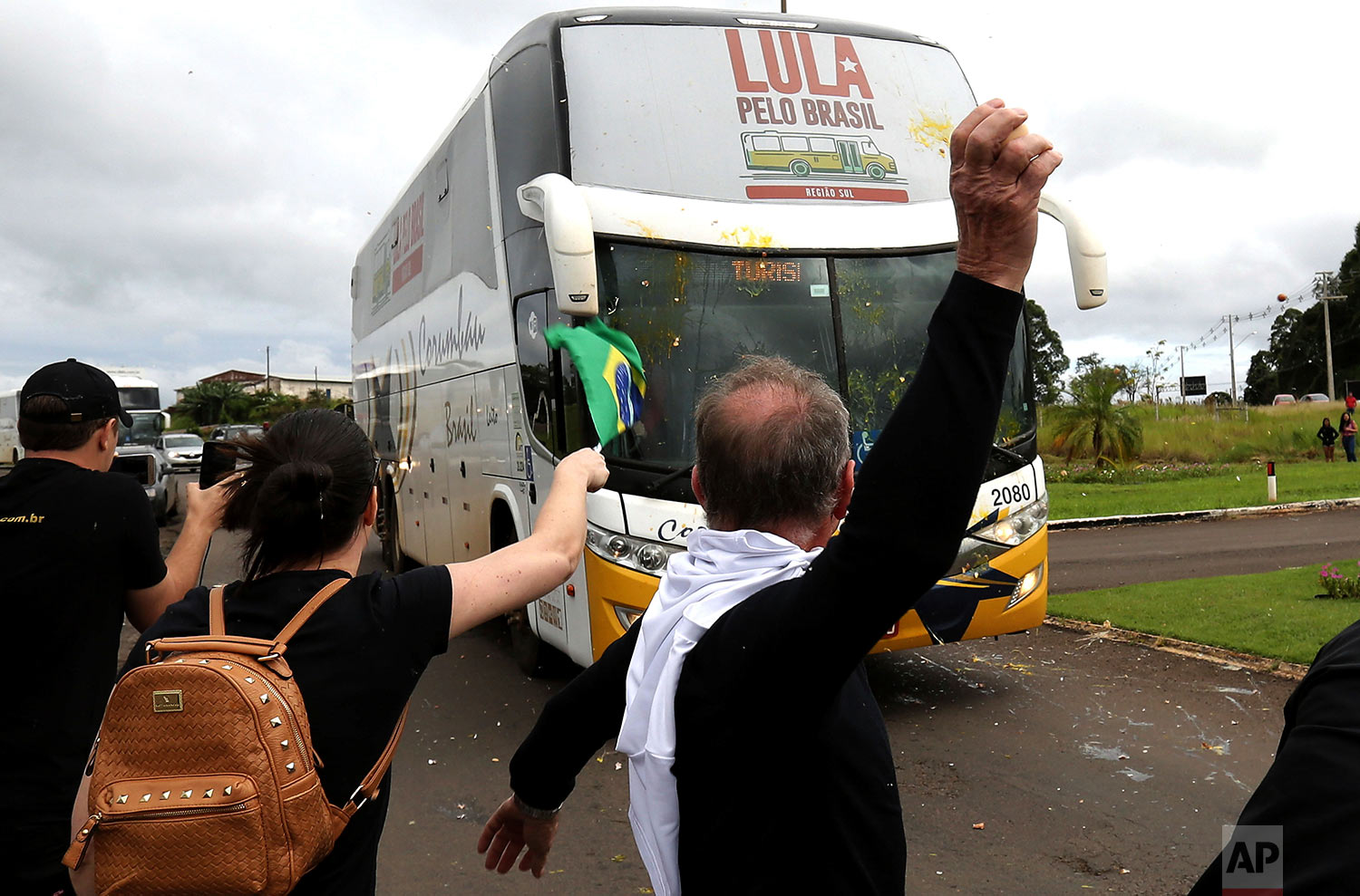 Opponents of Brazil's former President Luiz Inacio Lula da Silva throw eggs at his caravan arriving to Sao Miguel do Oeste in southern Brazil, March 25, 2018. The former leader is leading polls for October's presidential election but is likely to be barred from running and judges could order him to begin serving his sentence on a corruption conviction. (AP Photo/Eraldo Peres)