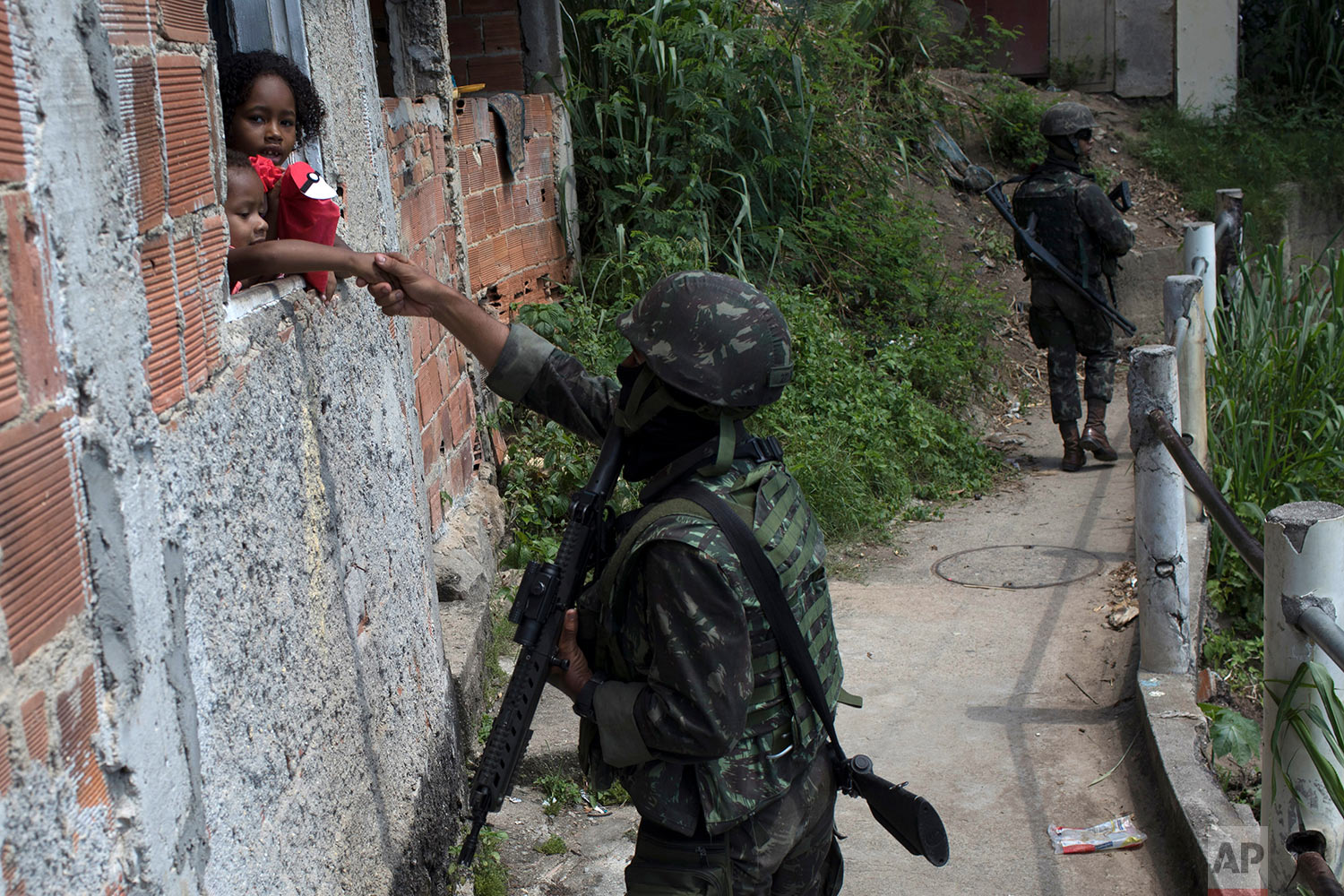 A soldier shakes the hand of a child while on patrol inside the Lins Complex of slums in Rio de Janeiro, Brazil, March 27, 2018. Troops and police are entering the complex in one of the largest operations since the military took control of security. (AP Photo/Leo Correa)