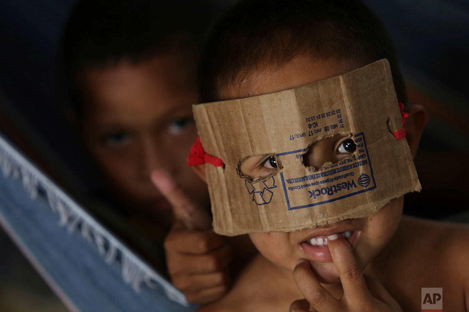 A Warao indigenous boy from Venezuela dons a mask fashioned from cardboard at a a shelter in Pacaraima, the main entry point for Venezuelans in the Brazilian state of Roraima, March 10, 2018. Opened late last year with the capacity to house about 250 people, the shelter, a former warehouse, today has upwards of 500, and more are arriving daily. (AP Photo/Eraldo Peres)