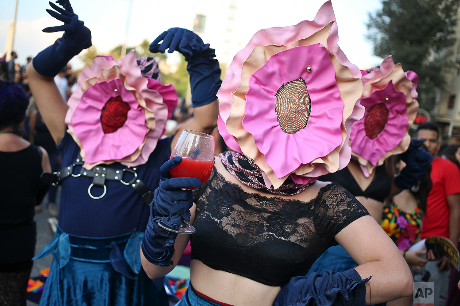 Women wearing masks in the likeness of vaginas perform during a march commemorating International Women's Day in Santiago, Chile, March 8, 2018. Many women stayed home from work, joined rallies or wore red Wednesday as International Women's Day was observed with a multitude of events around the world. (AP Photo/Esteban Felix)