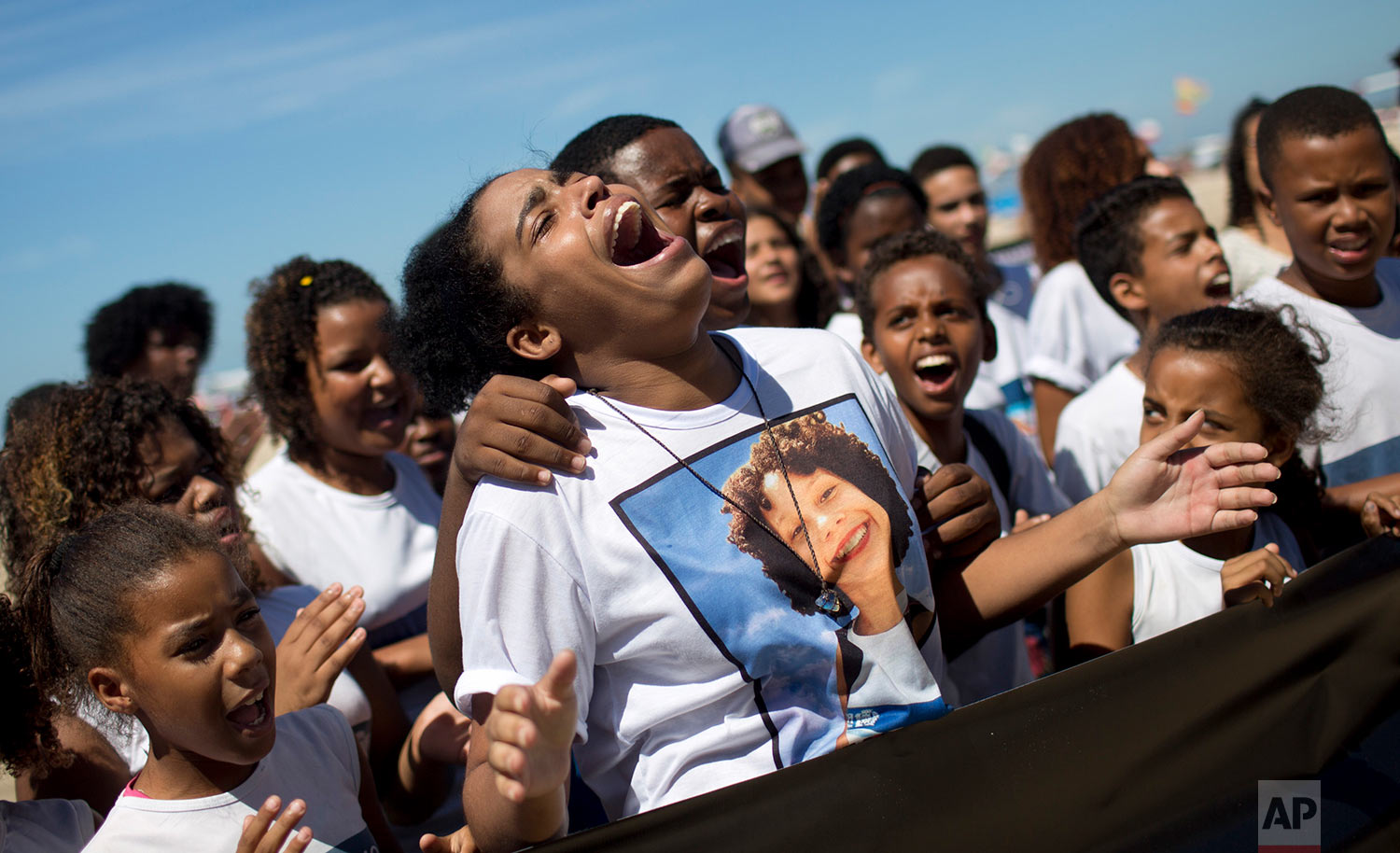 Bianca Alves da Costa, 21, center, sister of Maria Eduarda, who was shot to death inside her school, cries during a protest marking one year since her death, on Copacabana beach, in Rio de Janeiro, Brazil, March 30, 2018. Protesters marked the one-year anniversary of the death of the 13-year-old who was hit by stray bullets from a military police officer's rifle while drinking water from a fountain on her school's patio during gym class. (AP Photo/Silvia Izquierdo)