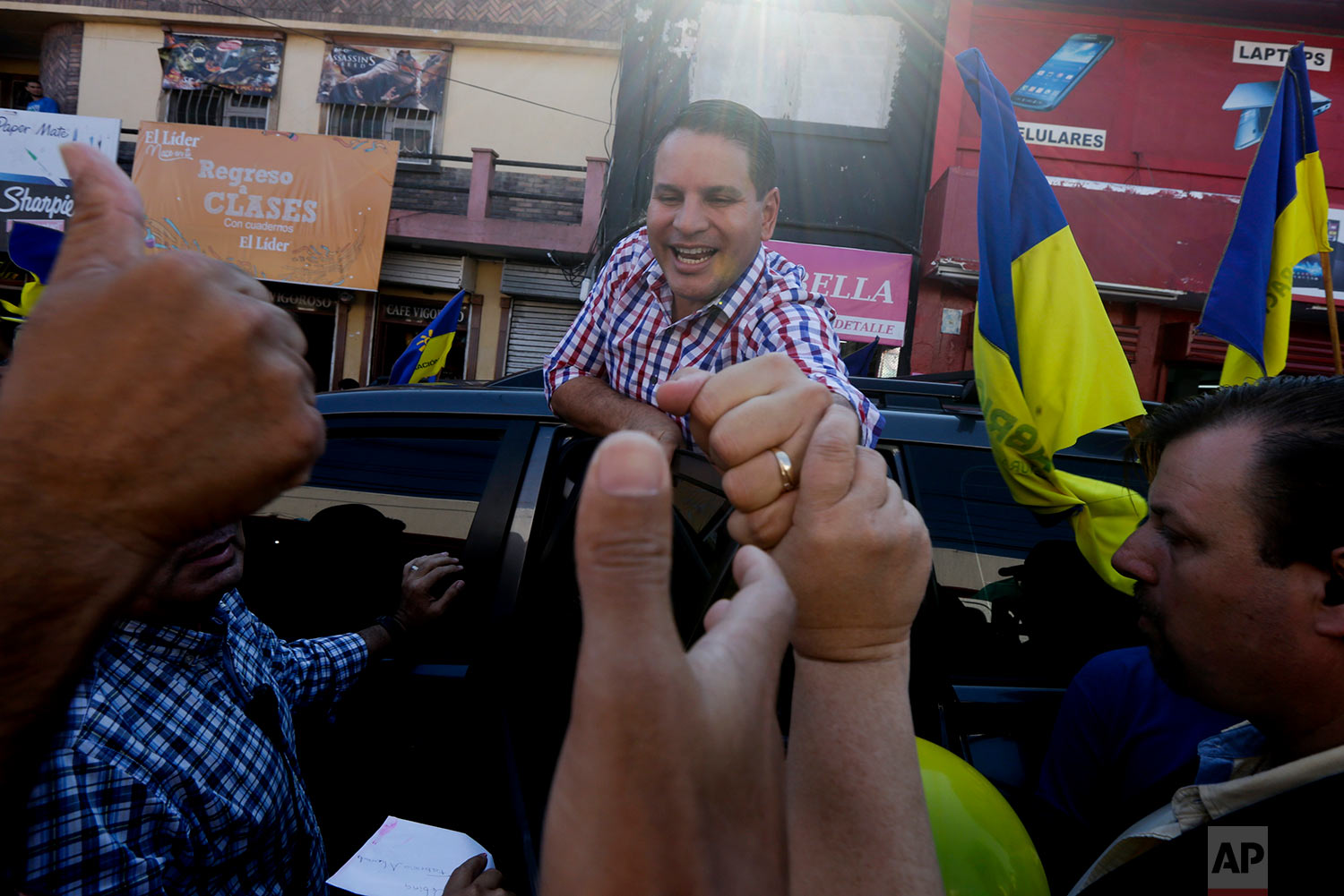 Presidential candidate Fabricio Alvarado, with the National Restoration party, greets supporters outside a market as he campaigns in Heredia, Costa Rica, March 28, 2018. Alvarado won the presidential runoff election on April 1. (AP Photo/Arnulfo Franco)