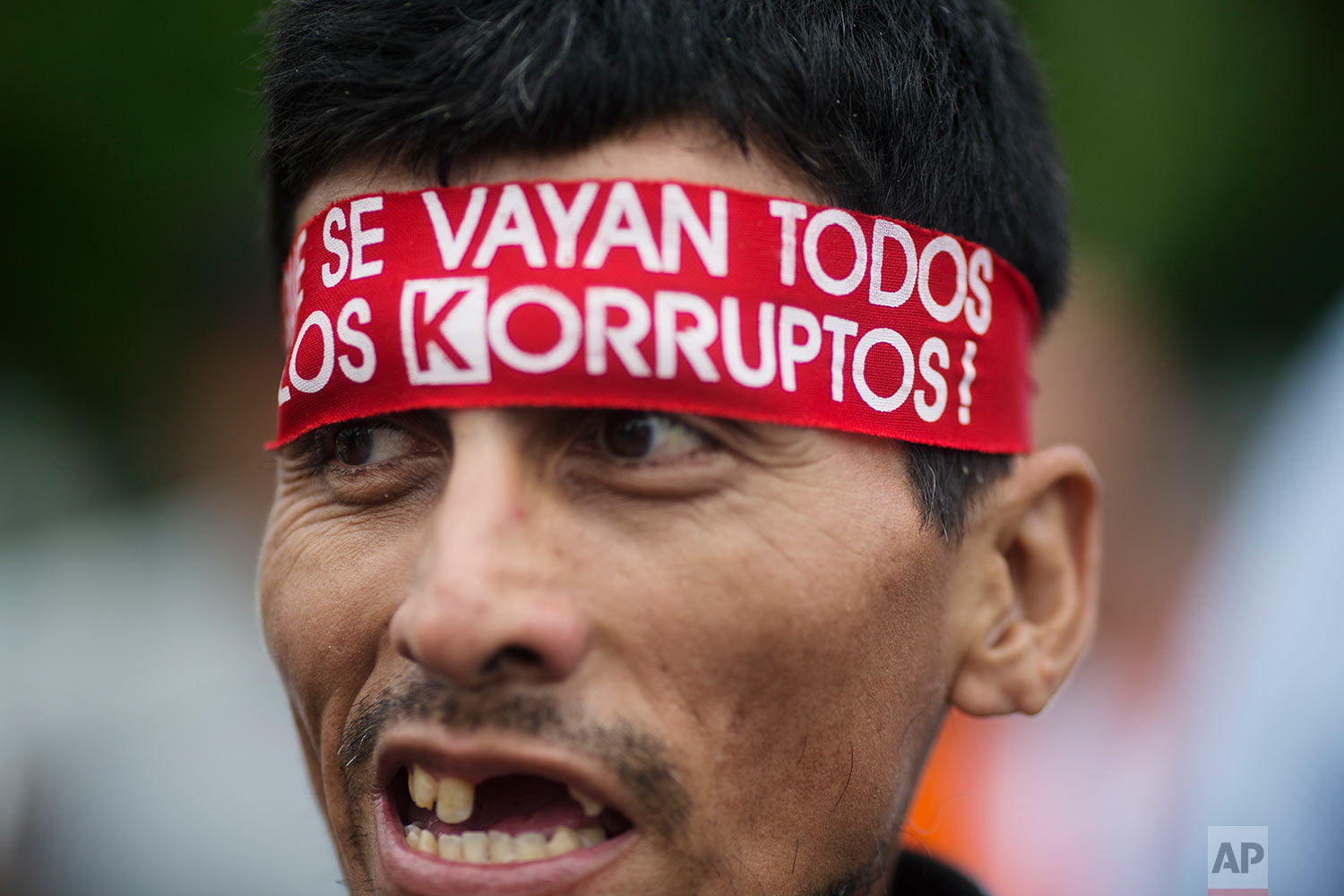 "A man wears a bandana with text that reads in Spanish ""Let all the corrupt go,"" during a protest against the country's political class, a day after the resignation of Peru's President Pedro Pablo Kuczynski, in Lima, Peru, March 22, 2018. Peru's congress is gearing up to consider whether or not to accept Kuczynski's resignation following the release of several videos appearing to show allies offering state contracts in exchange for votes against his pending impeachment. (AP Photo/Rodrigo Abd)"